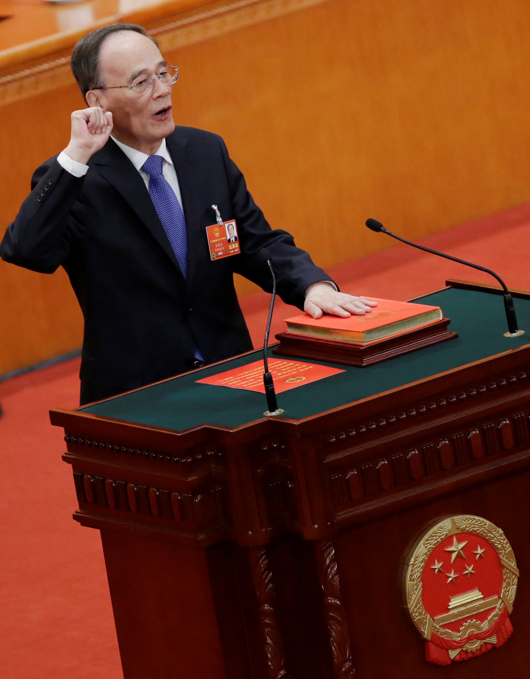 Newly elected Chinese Vice President Wang Qishan with his hand on the Constitution takes the oath at the fifth plenary session of the National People's Congress (NPC) at the Great Hall of the People in Beijing, China March 17, 2018.