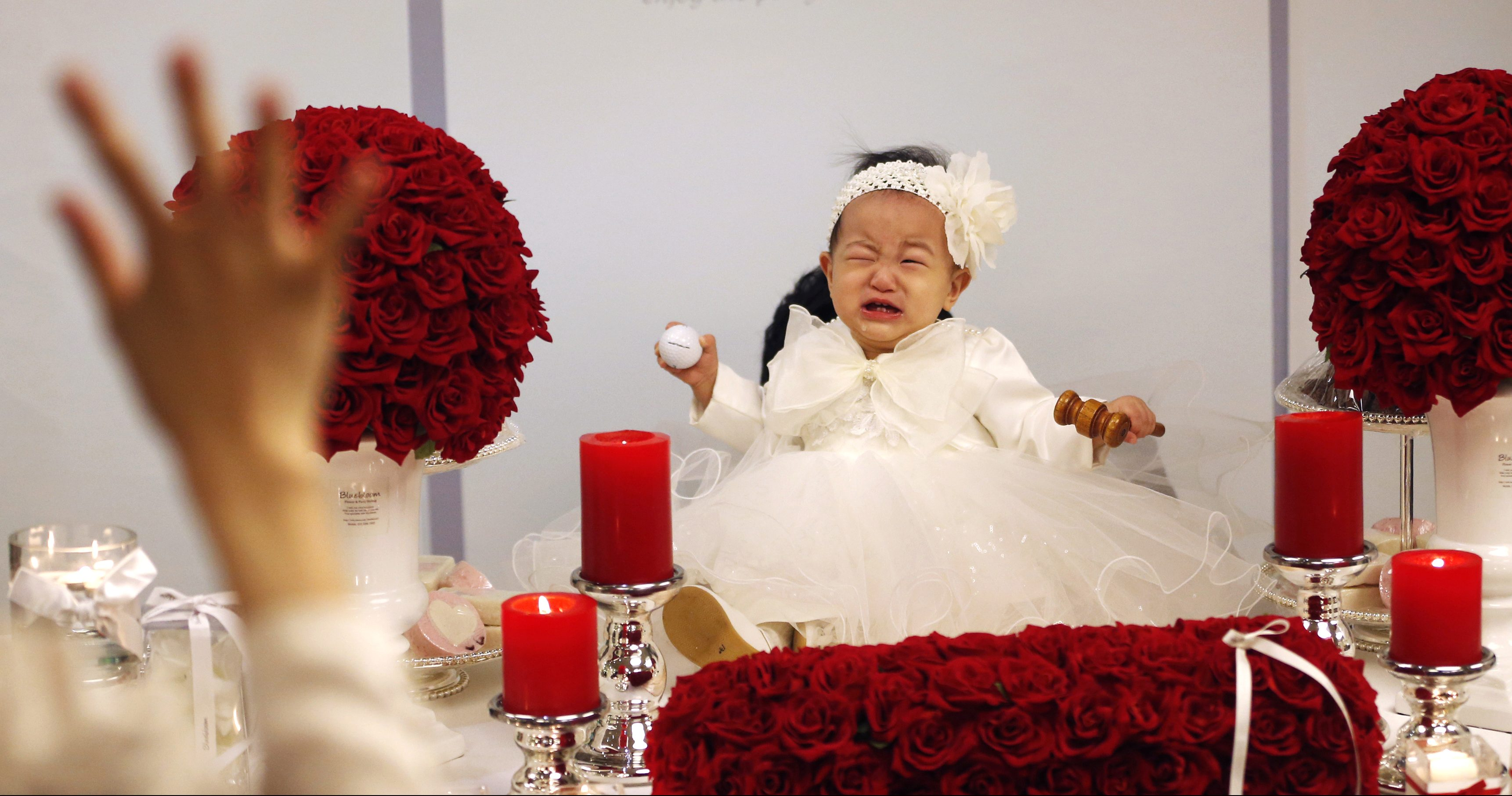 Kim Dot-byul cries as she poses for photographs during her first birthday party or Doljanchi in Korean in Seoul