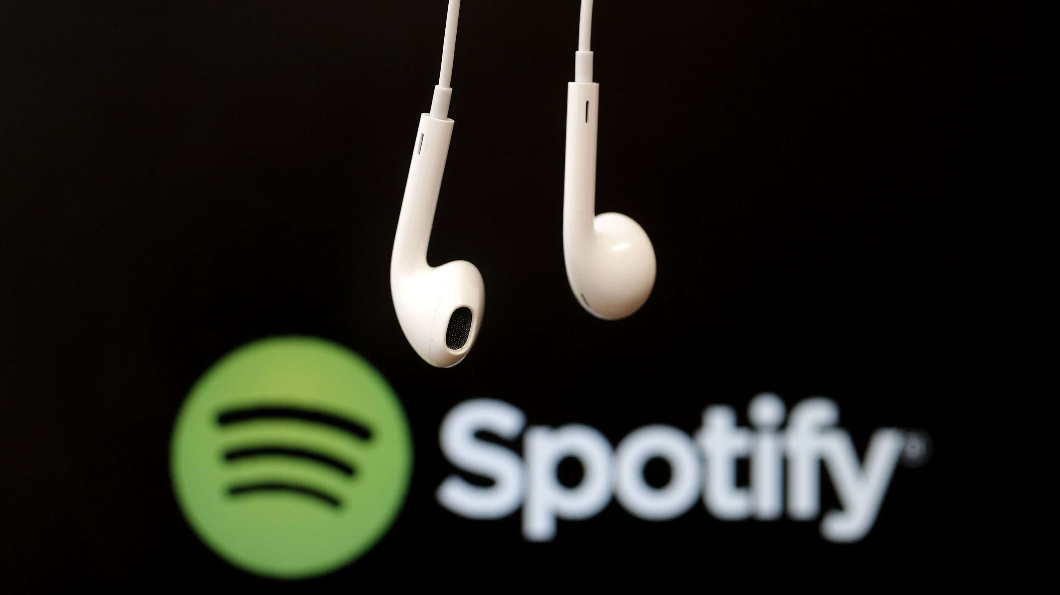 Headphones are seen in front of a logo of online music streaming service Spotify in this illustration picture taken in Strasbourg, February 18, 2014. Spotify is recruiting a U.S. financial reporting specialist, adding to speculation that the Swedish start-up is preparing for a share listing, which one banker said could value the firm at as much as $8 billion. REUTERS/Christian Hartmann (FRANCE - Tags: BUSINESS ENTERTAINMENT LOGO) - GM1EA2I1FZ401