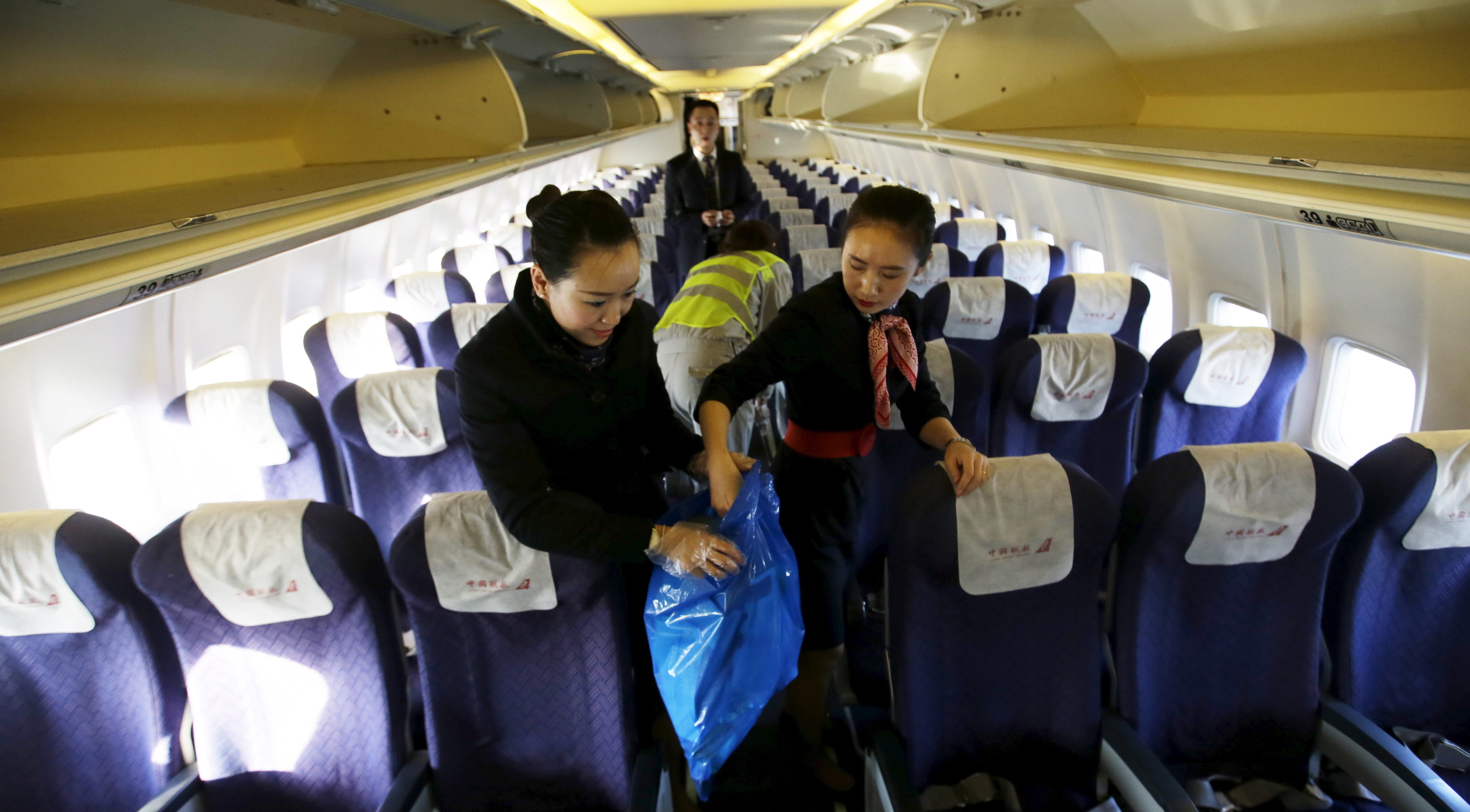 Chief flight attendant Han Juanjuan (L) and her colleague Wang Xin (R) clean the cabin of a China United Airlines aircraft after it landed at the Nanyuan Airport in Beijing, China, December 4, 2015. Picture taken December 4, 2015.      To match CHINA-AIRLINES/LOW-COST       REUTERS/Jason Lee - GF20000084624