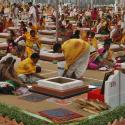 """Hindu priests and devotees sit around decorated """"havan kunds"""" as they pray at a temple on the outskirts of Ahmedabad"""