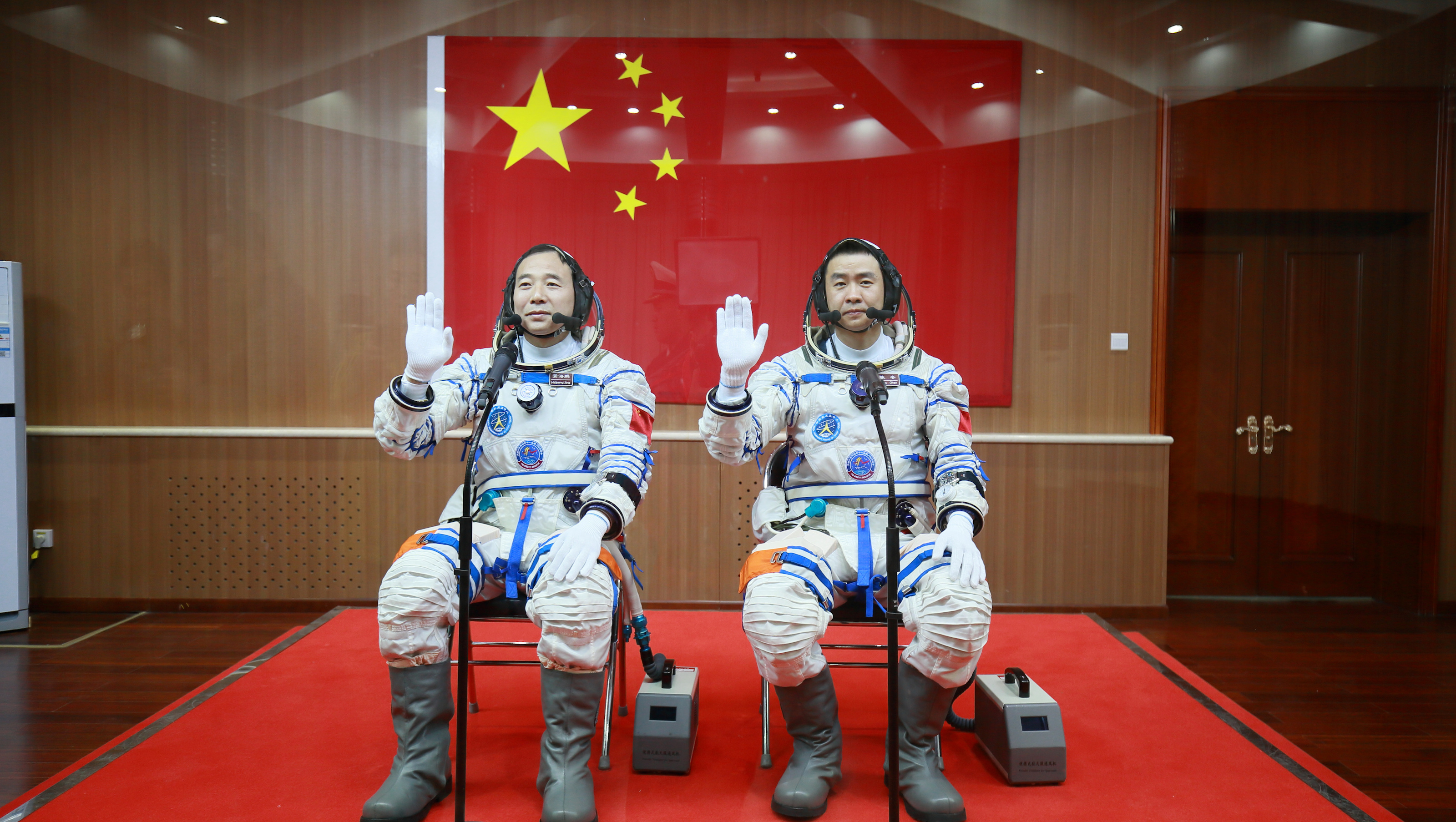 Chinese astronauts Jing Haipeng (L) and Chen Dong wave in front of a Chinese national flag before the launch of  Shenzhou-11 manned spacecraft, in Jiuquan, China, October 17, 2016. REUTERS/Stringer ATTENTION EDITORS - THIS PICTURE WAS PROVIDED BY A THIRD PARTY. EDITORIAL USE ONLY. CHINA OUT. NO COMMERCIAL OR EDITORIAL SALES IN CHINA. - D1AEUHLRNRAB