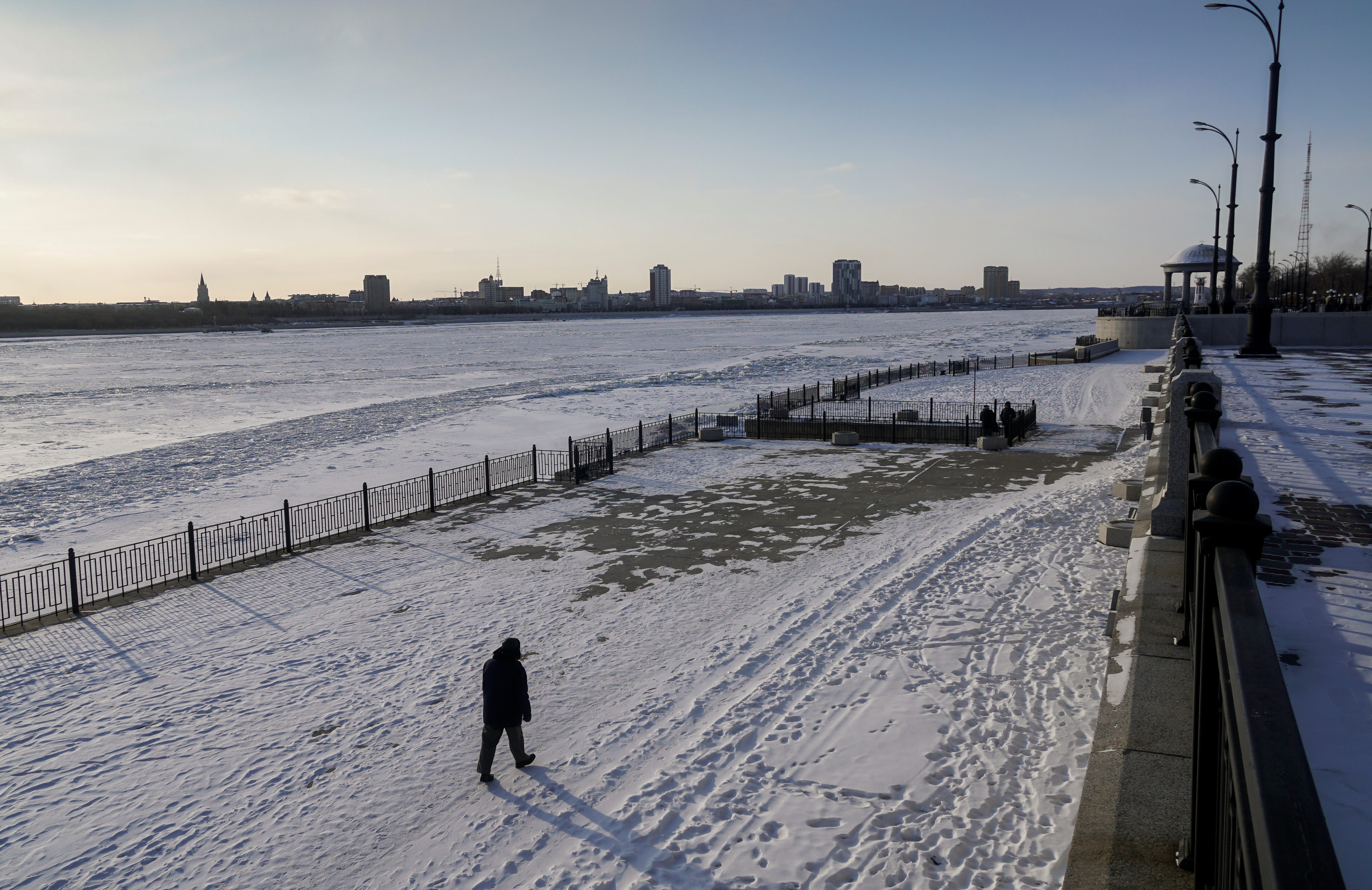 A man walks along an embankment of the Amur river.