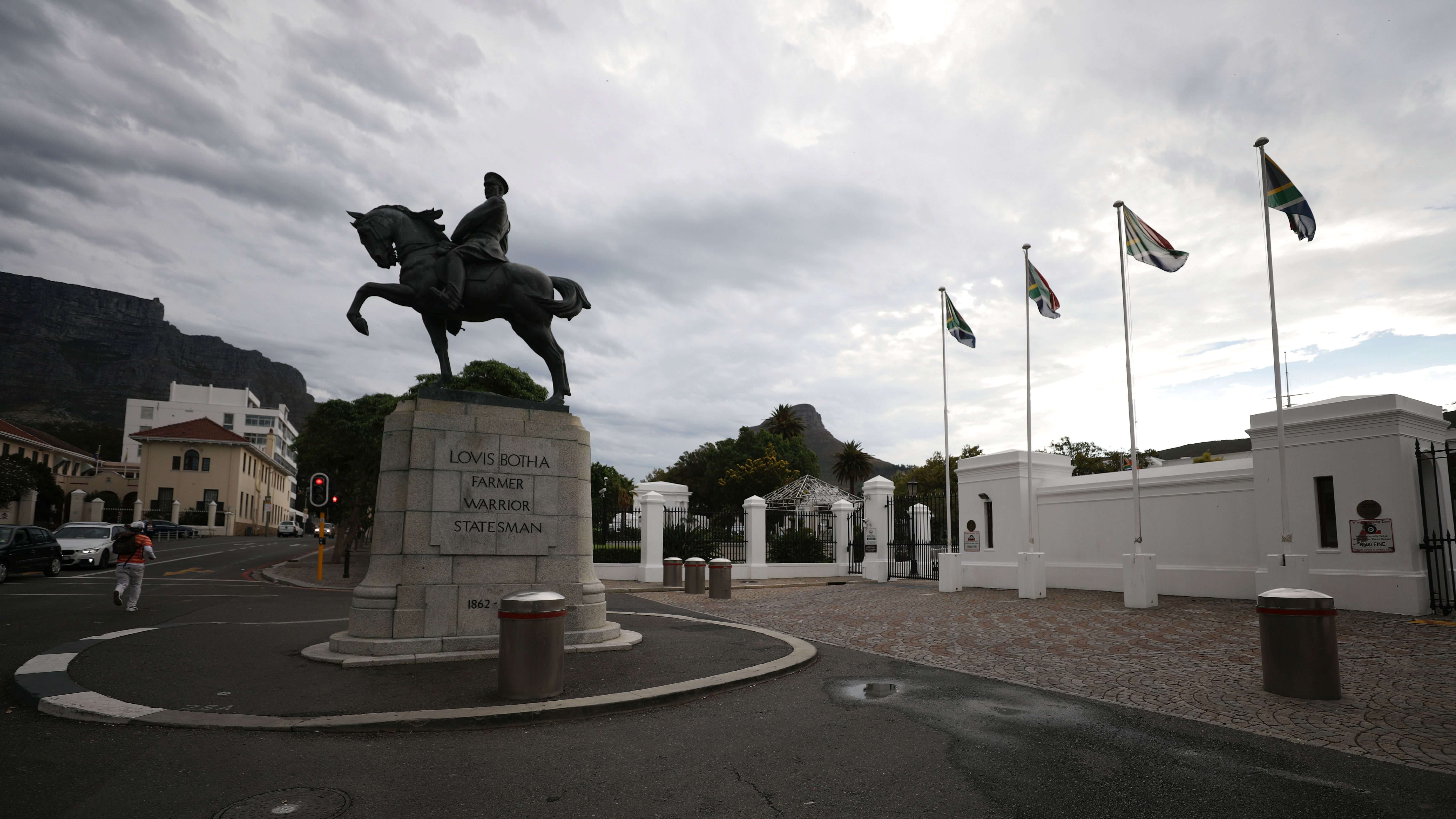 Flags fly behind the statue of Louis Botha, South Africa's first Prime Minister, outside Parliament in Cape Town, South Africa, February 13, 2018.