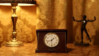 A 1950's Swiss made travel alarm clock sits on a bedside table