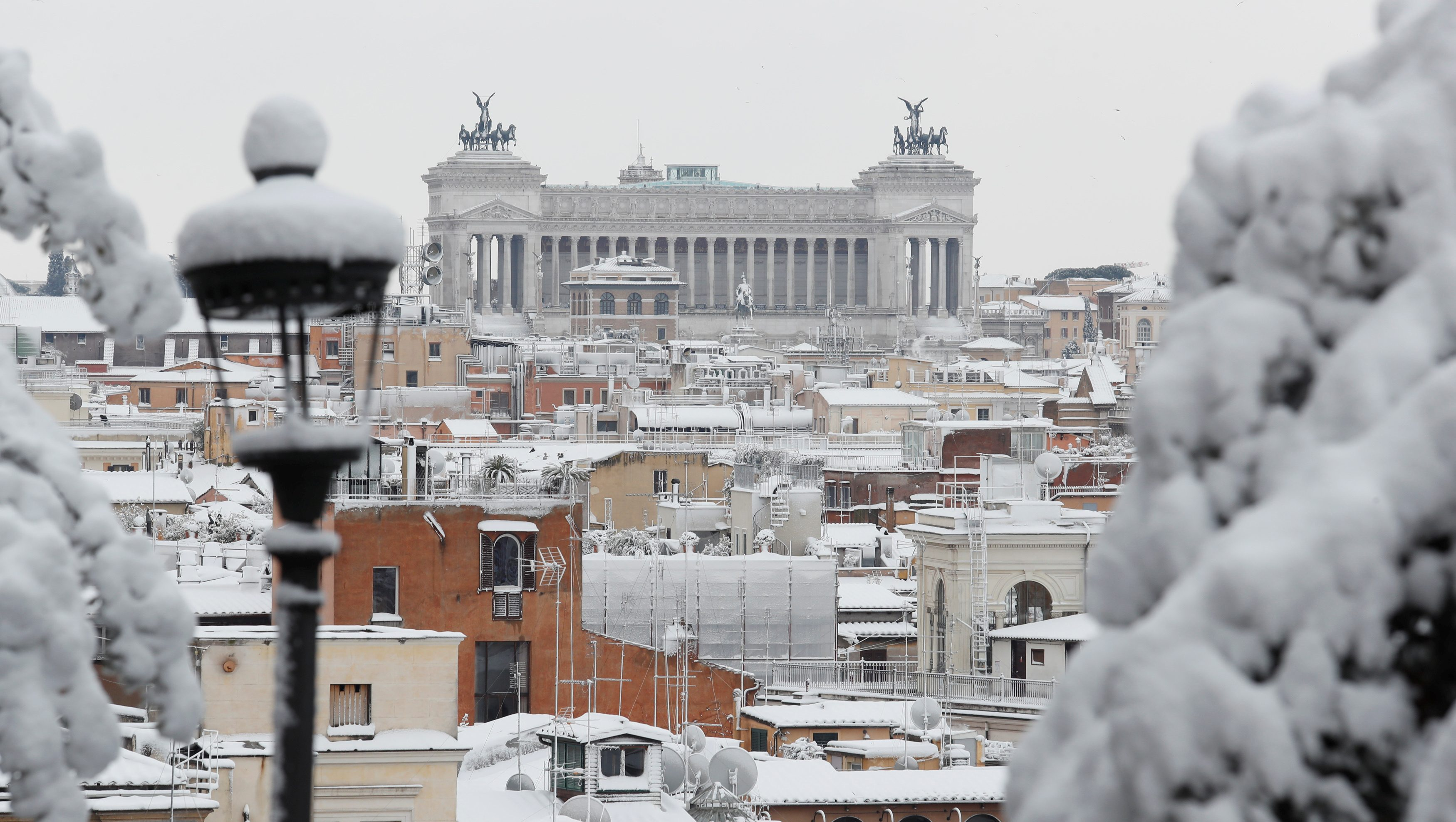 Roofs are seen covered in snow during a heavy snowfall in downtown Rome