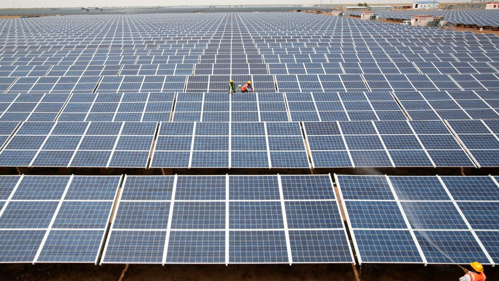 FILE PHOTO: Workers install photovoltaic solar panels at the Gujarat solar park under construction in Charanka village, in Patan district of the western Indian state of Gujarat, India, April 14, 2012. REUTERS/Amit Dave/File photo - RC1183C92C60