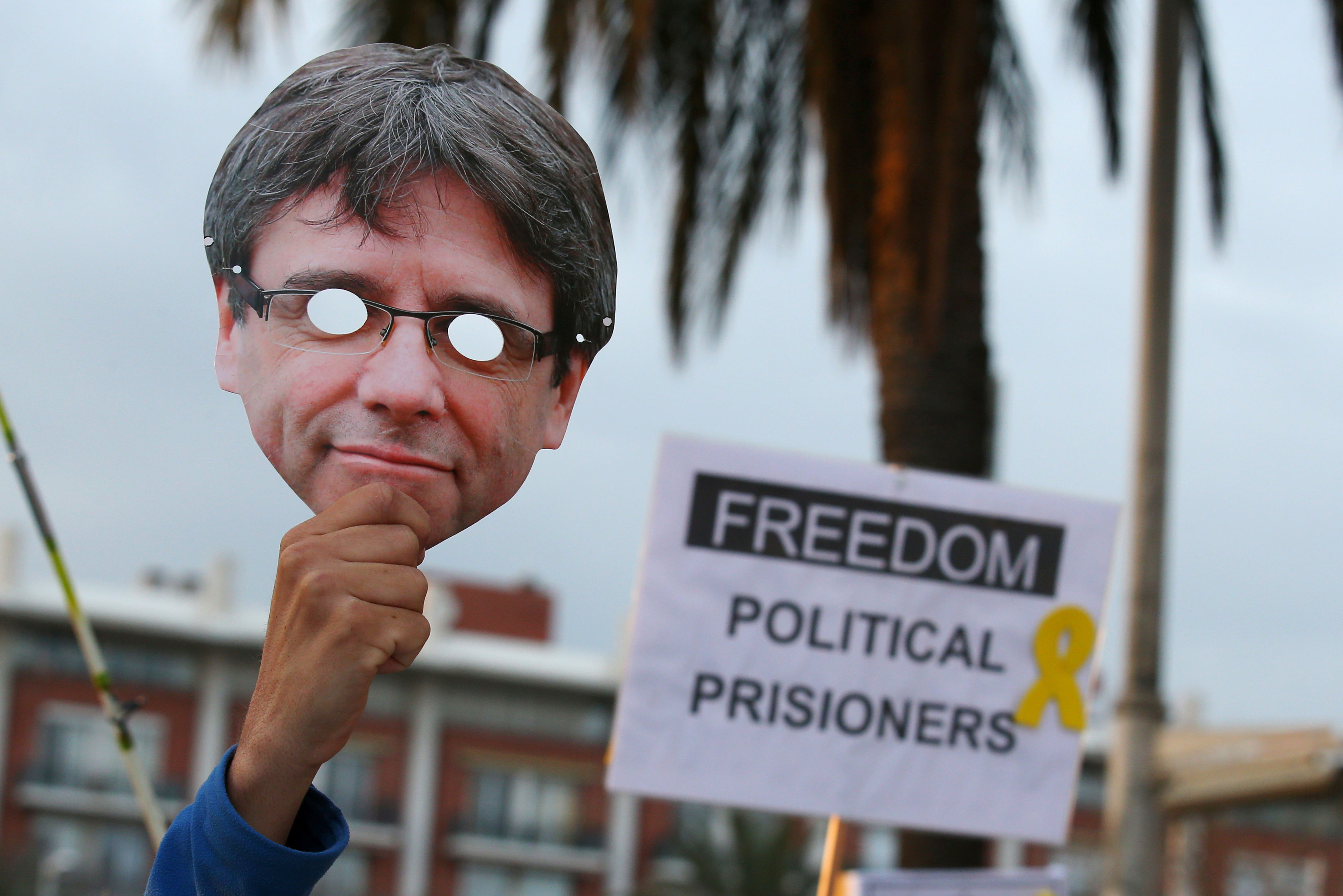 A man raises up a Puigdemont's mask during a protest in front of Germany's Consulate after former president Carles Puigdemont was detained in Germany, during a demonstration held by pro-independence associations in Barcelona, Spain March 25, 2018. REUTERS/Albert Gea - RC1A4D55B180