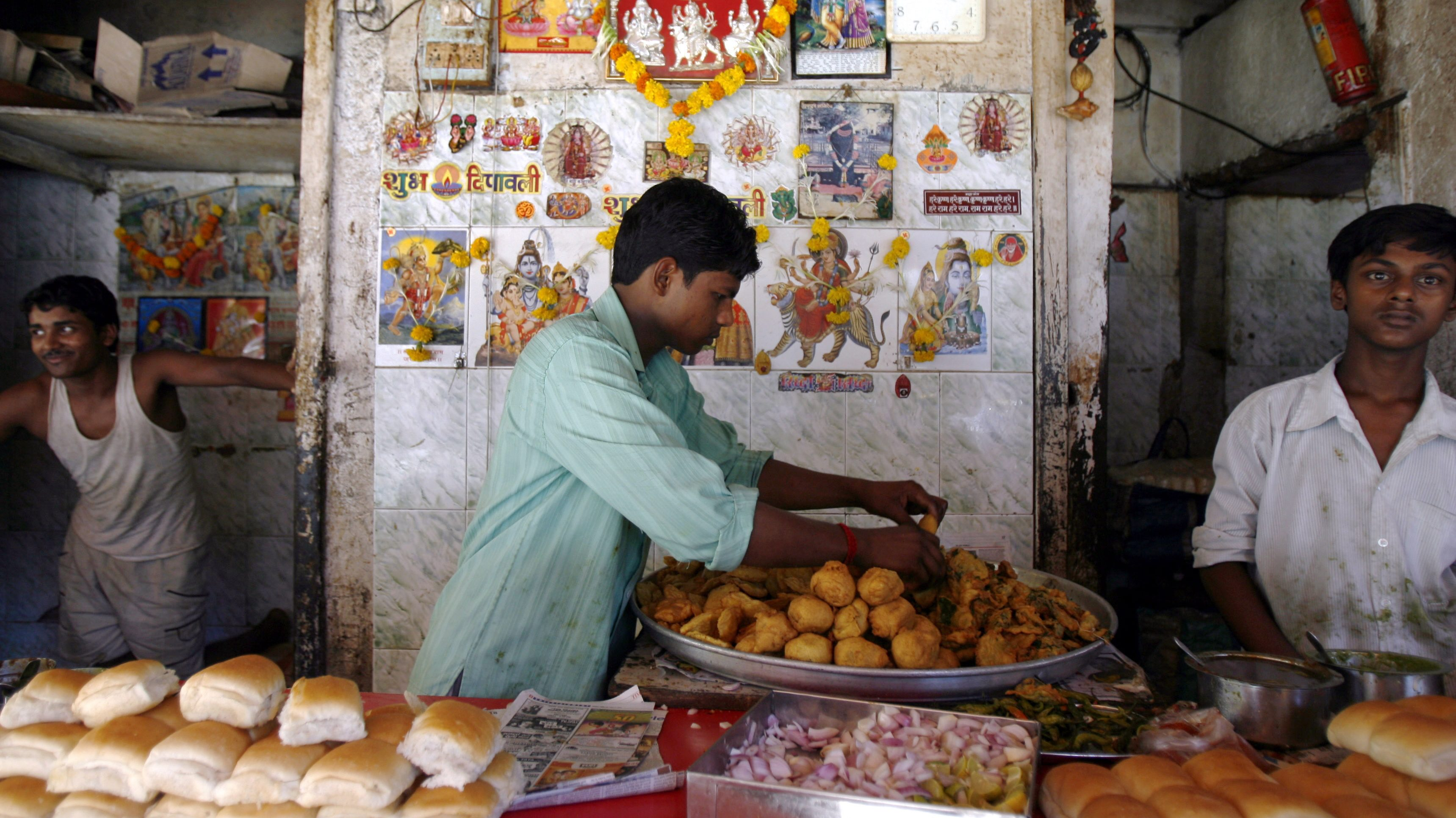 Vendor arranges vada Pav, a spicy potato ball fried in batter and served in a bun, at a street-side snack stall in Mumba