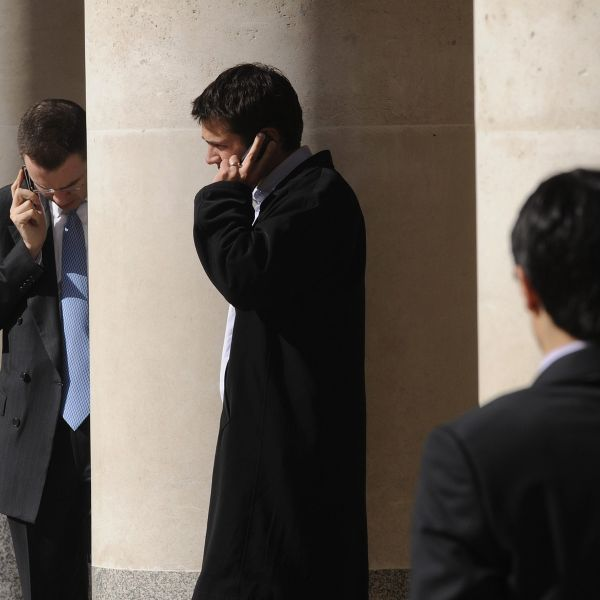 City workers make phone calls outside the London Stock Exchange in Paternoster Square in the City of London at lunchtime October 1, 2008.