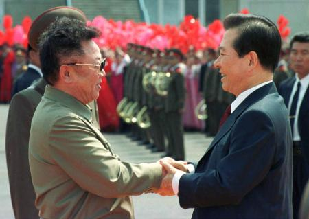 North Korean leader Kim Jong-il (L) shakes hands with South Korea's President Kim Dae-jung as the latter arrives at Pyongyang's Sunan airport June 13, 2000.