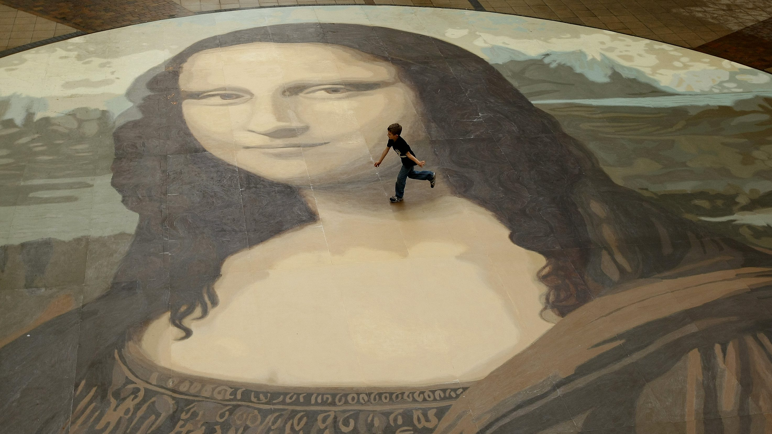 A boy runs across a giant copy of the Mona Lisa as it is unveiled in Wrexham, north Wales, October 28, 2009. The giant version of Leonardo da Vinci's masterpiece measuring 17.5 metres across and 50 times bigger than the original, is an attempt to produce the largest ever reproduction of the painting.