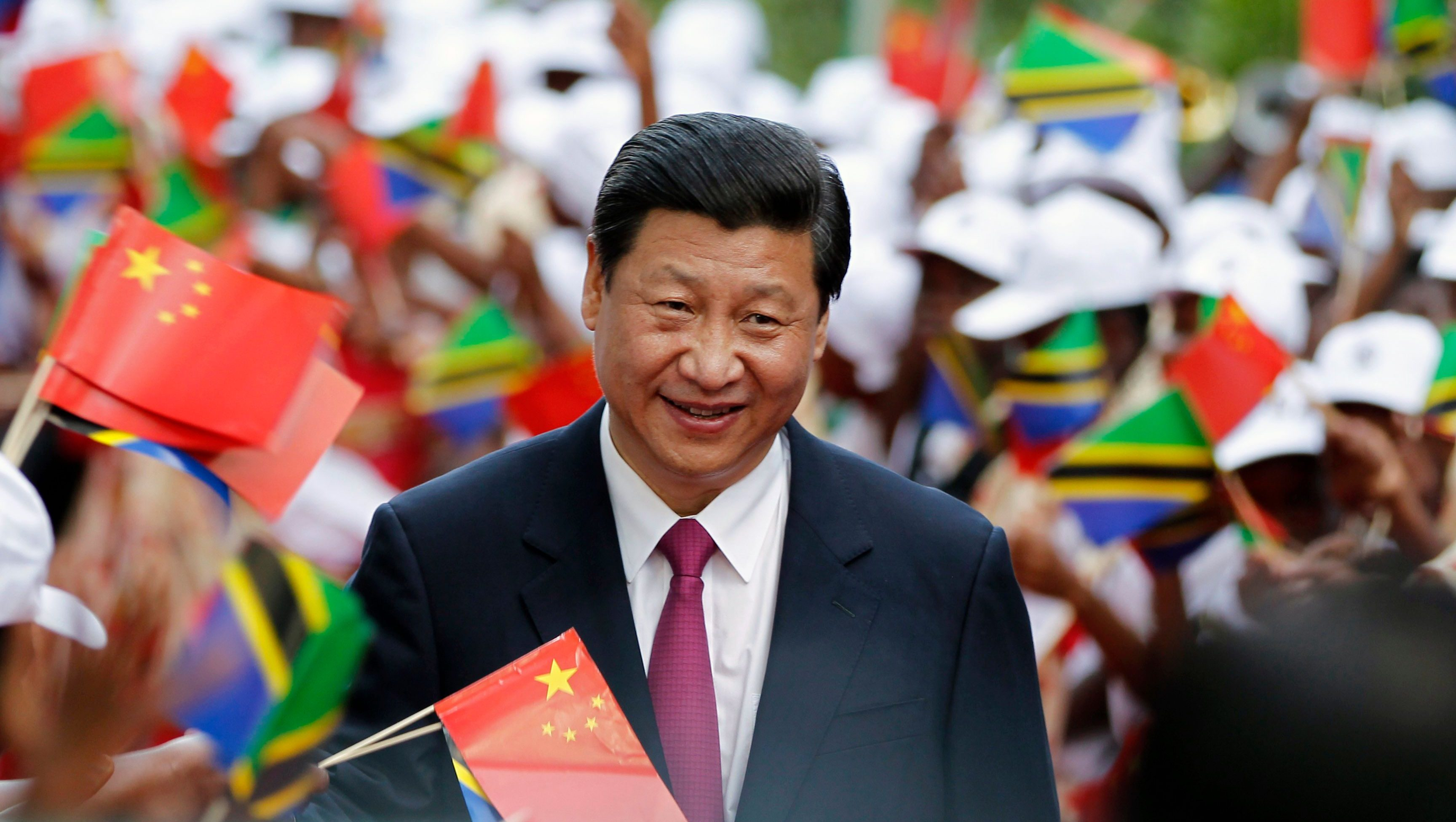 China's President Xi Jinping walks through Tanzanian women waving flags as he is welcomed at the State House in Dar es Salaam, March 24, 2013. Xi faces growing calls from policymakers and economists in Africa for a more balanced trade relationship between the continent and China as he arrives in Tanzania at the beginning of an African tour on Sunday.