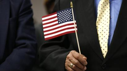 An immigrant holds a U.S. flag during a naturalization ceremony in New York