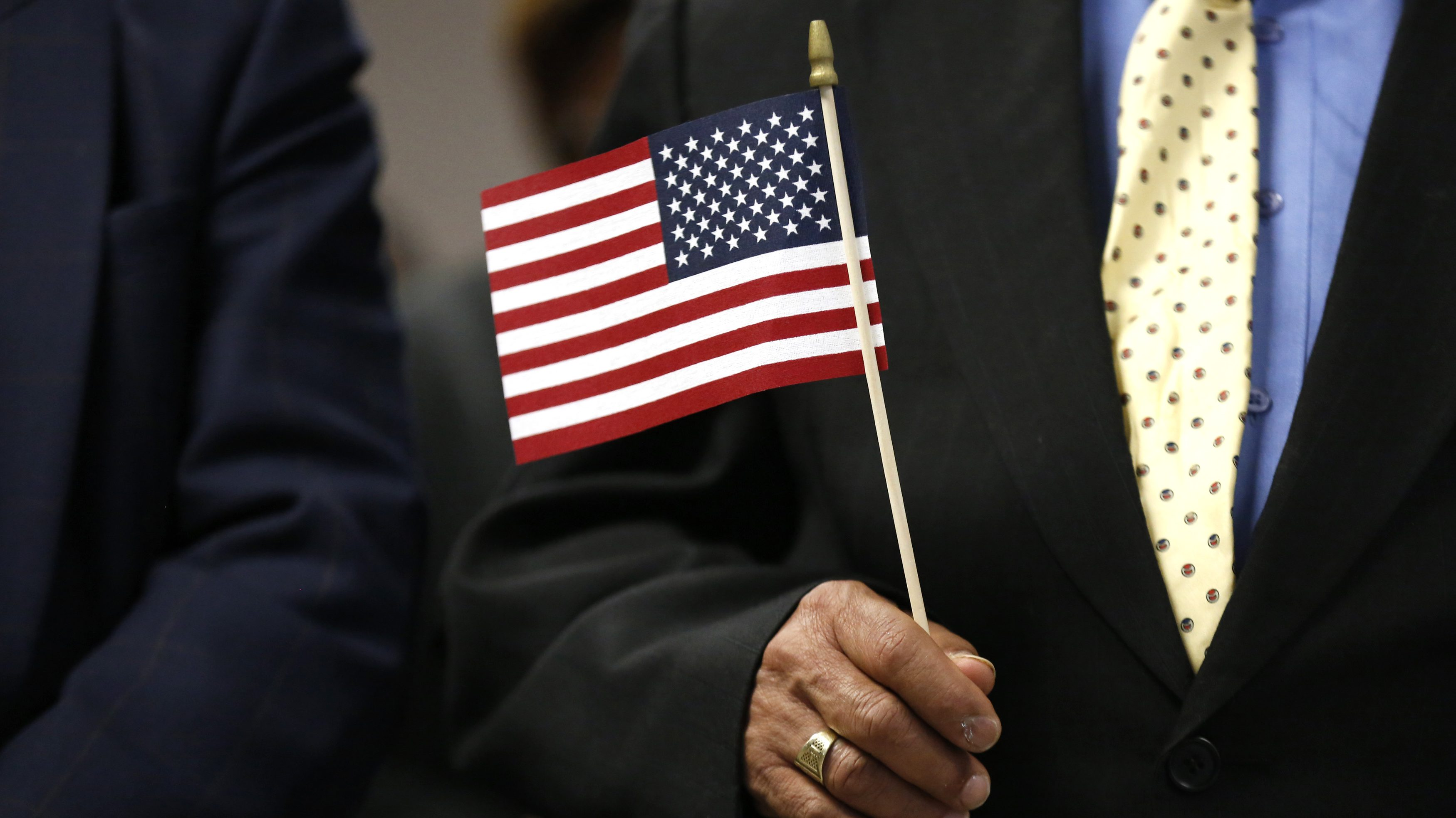 """An immigrant holds a U.S. flag during a naturalization ceremony to become an American citizen in New York, April 17, 2013. President Barack Obama on Tuesday embraced a sweeping overhaul of the nation's immigration system put forward by a bipartisan group of senators, saying it was """"largely consistent"""" with his own principles for immigration reform. REUTERS/Brendan McDermid (UNITED STATES - Tags: SOCIETY IMMIGRATION POLITICS) - GM1E94I0A4302"""