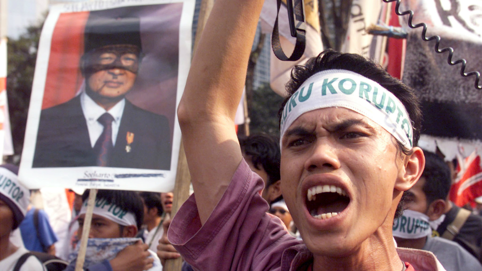 Indonesian protesters shout slogans and carry a poster of former president Suharto as they march though the streets of Jakarta May 12. Hundreds of students took to the streets on Friday to mark the second anniversary of bloody riots which helped to topple former President Suharto. Social and economic chaos and protests by tens of thousands of students demanding democratic reforms helped bring Suharto's army-backed rule to an end on May 21, 1998.