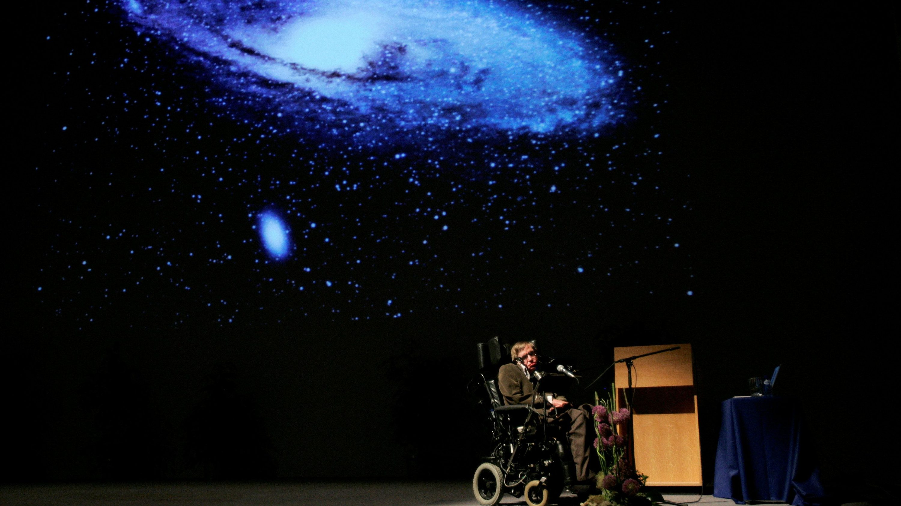 "British physicist Stephen Hawking delivers a lecture on ""The Origin of the Universe"" at the Heysel conference hall in Brussels in 2007"