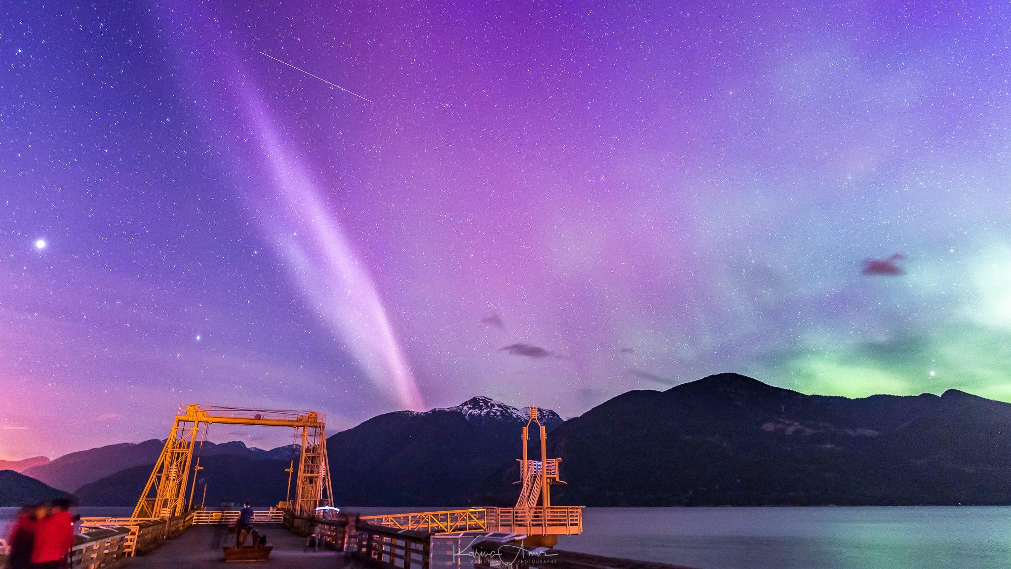 A pink aurora lights up a purple sky