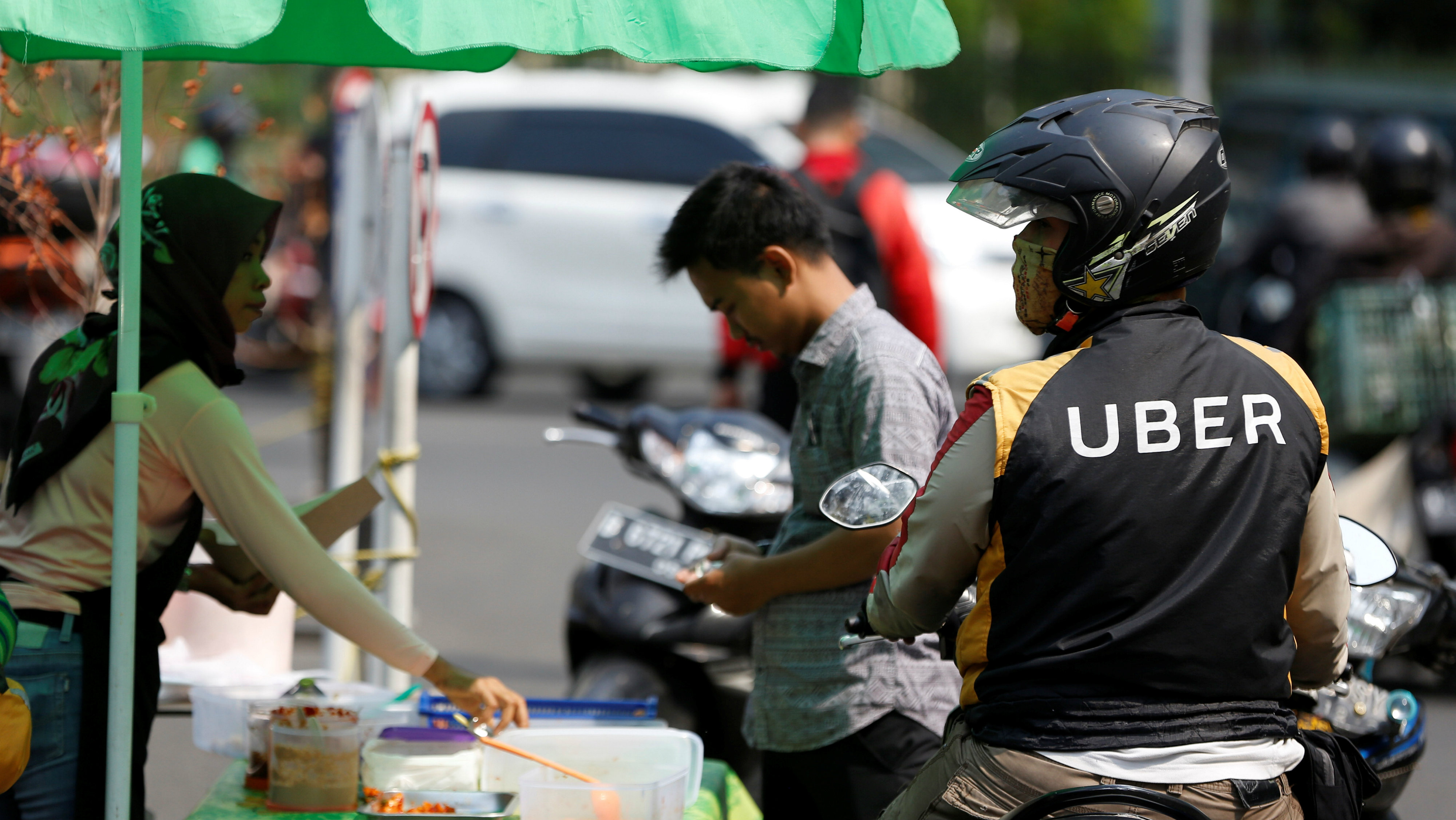 An Uber motorcycle taxi driver stops at a food stall next to a shopping mall in Jakarta, Indonesia
