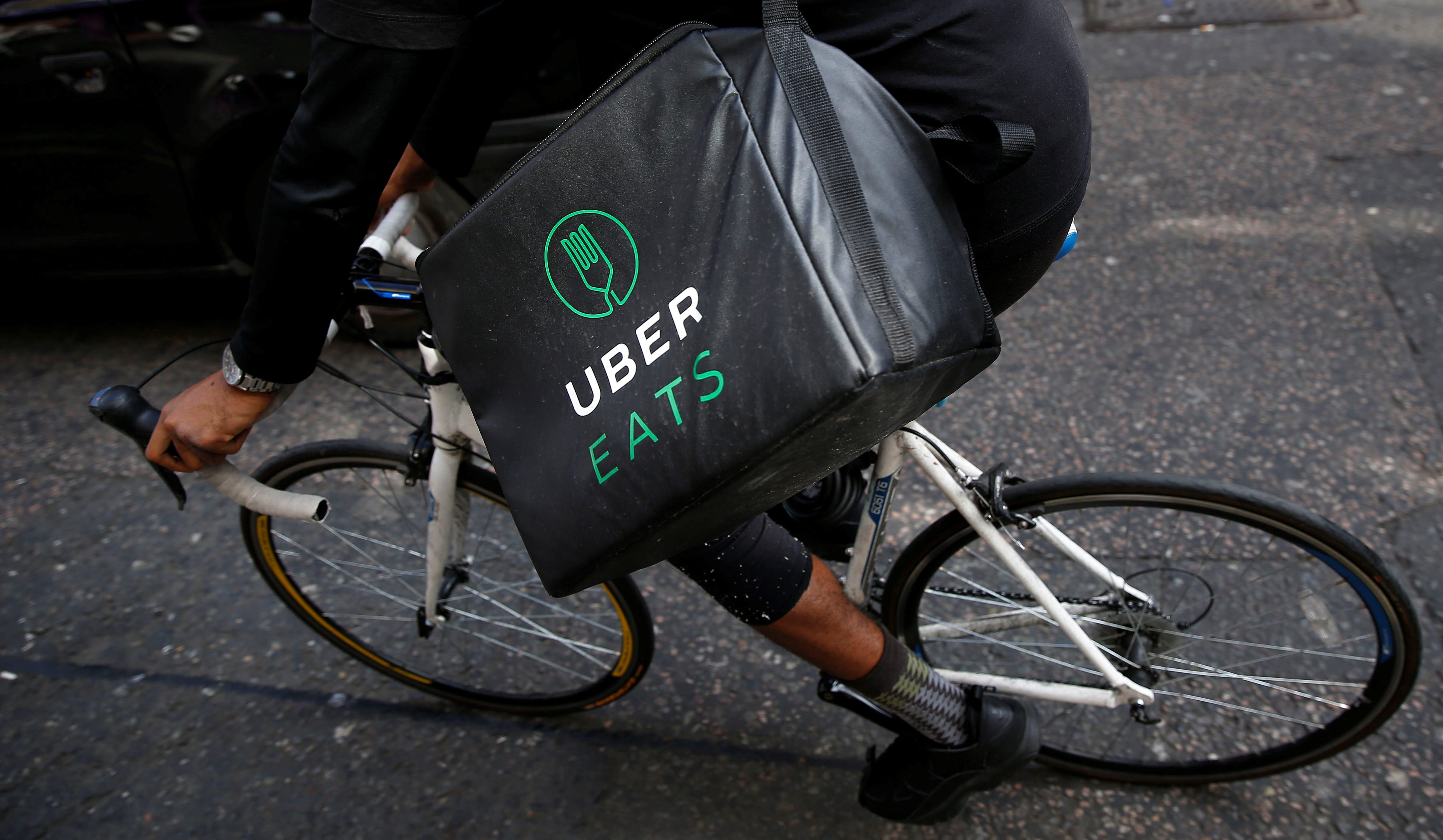 An UberEATS food delivery courier rides his bike in London, Britain September 7, 2016. Picture taken September 7, 2016. To match FOOD-DELIVERY/  REUTERS/Neil Hall - D1BEUDSKIIAA
