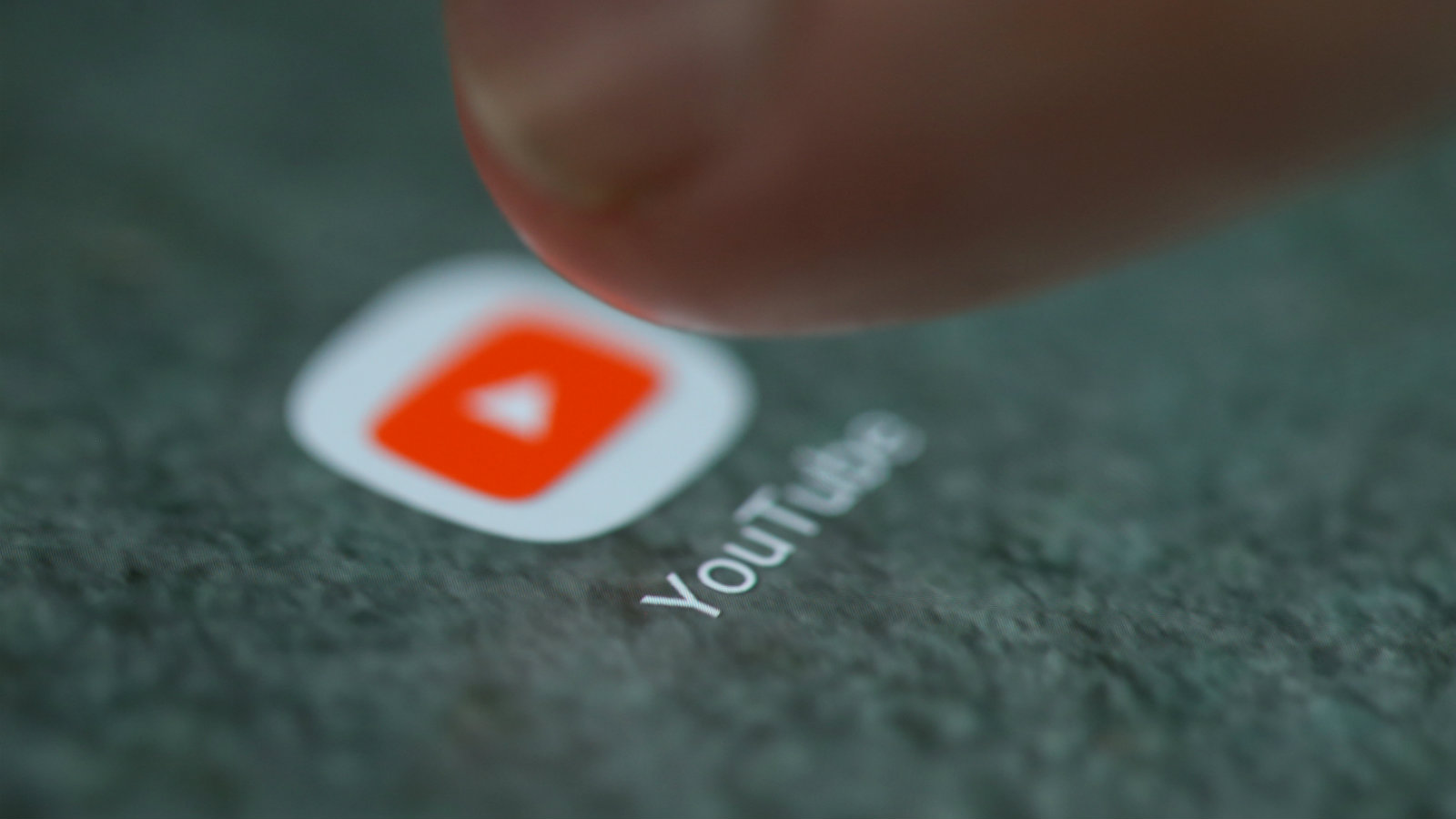 The YouTube app logo on a smartphone.