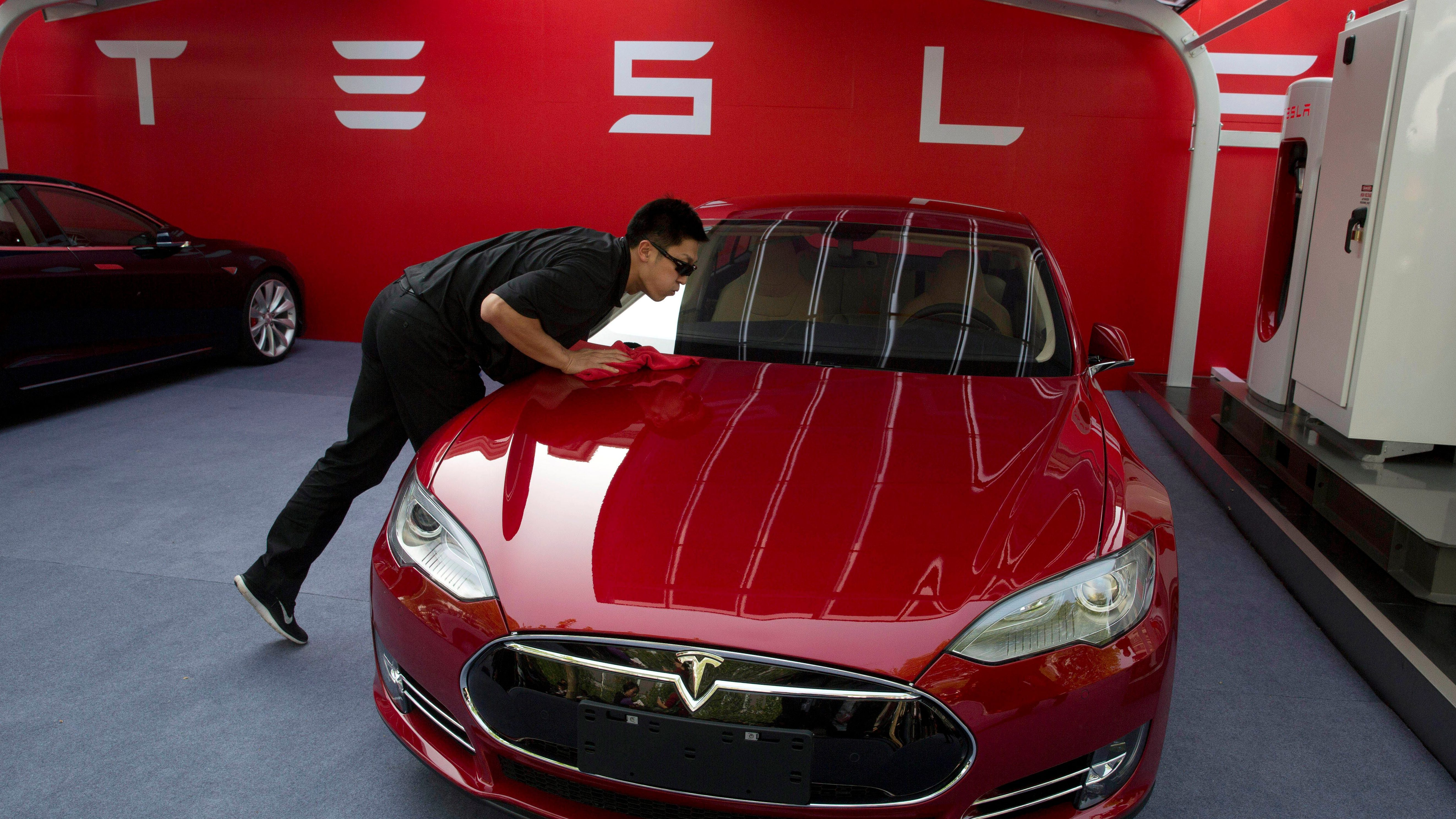 A worker cleans a Tesla Model S sedan before a event to deliver the first set of cars to customers in Beijing. Tesla Motors on Thursday, March 19, 2015 said it is updating its Model S electric car to help ease drivers' worries about running out of battery charge.