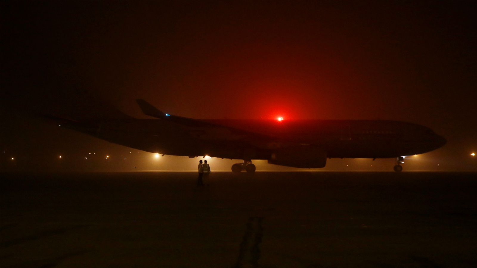 Airport staff stand as Britain's Prime Minister Theresa May's aircraft arrives amid the heavy smog at the airport in New Delhi, India, November 6, 2016.