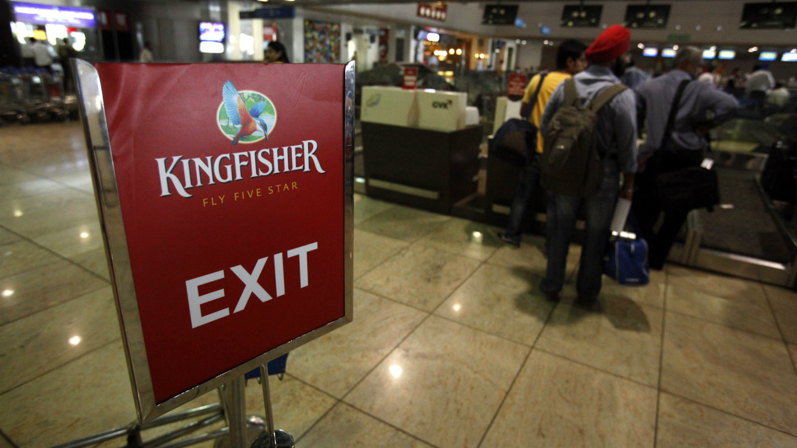 Kingfisher Airlines customers wait in a check-in queue at Mumbai's domestic airport March 20, 2012. India's aviation minister warned Kingfisher Airlines that its licence may be cancelled if safety norms and financial viability conditions are not met, in the latest blow to the beleaguered carrier.