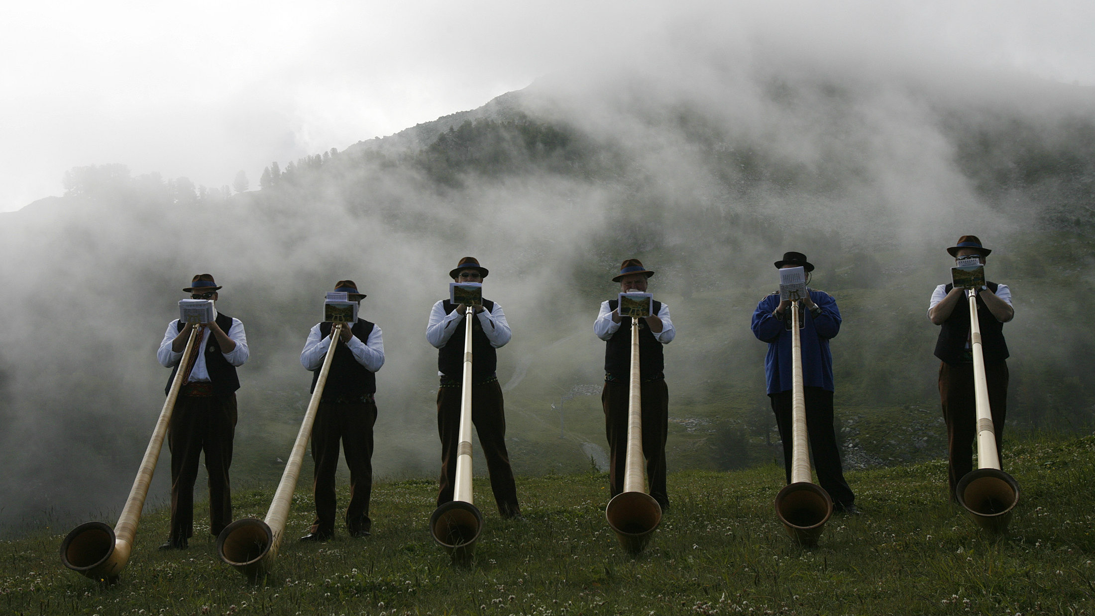 Alphorn blowers practice early morning before the International Alphorn contest on the alp Tracouet in Nendaz, southern Switzerland July 22, 2007. The annual musical contest, with 'solo', 'group' and 'best over the past year' competition categories, takes place over three days.