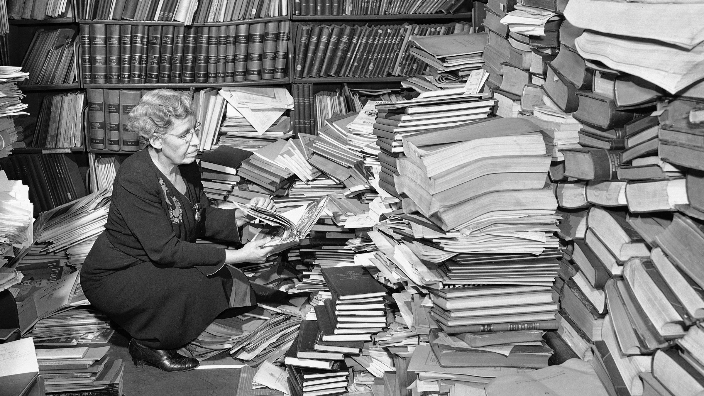 Woman going through huge stack of books