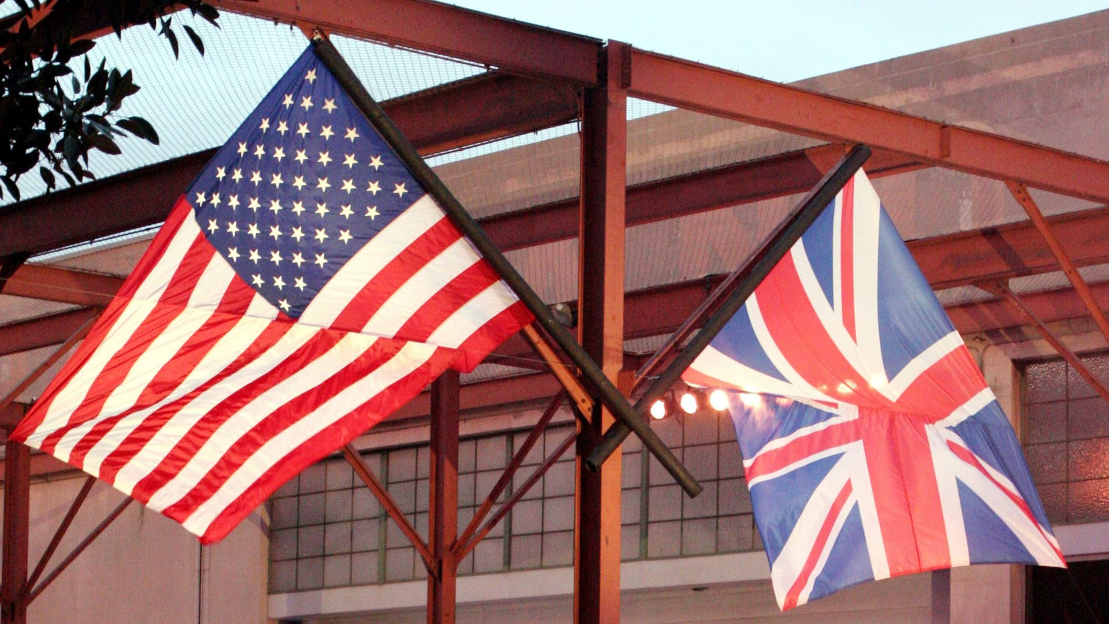 An American and British flag fly as a valet runs past photographers during a private party held in honor of David and Victoria Beckham at the Museum of Contemporary Art, Sunday, July 22, 2007, in Los Angeles. (AP Photo/Rene Macura)