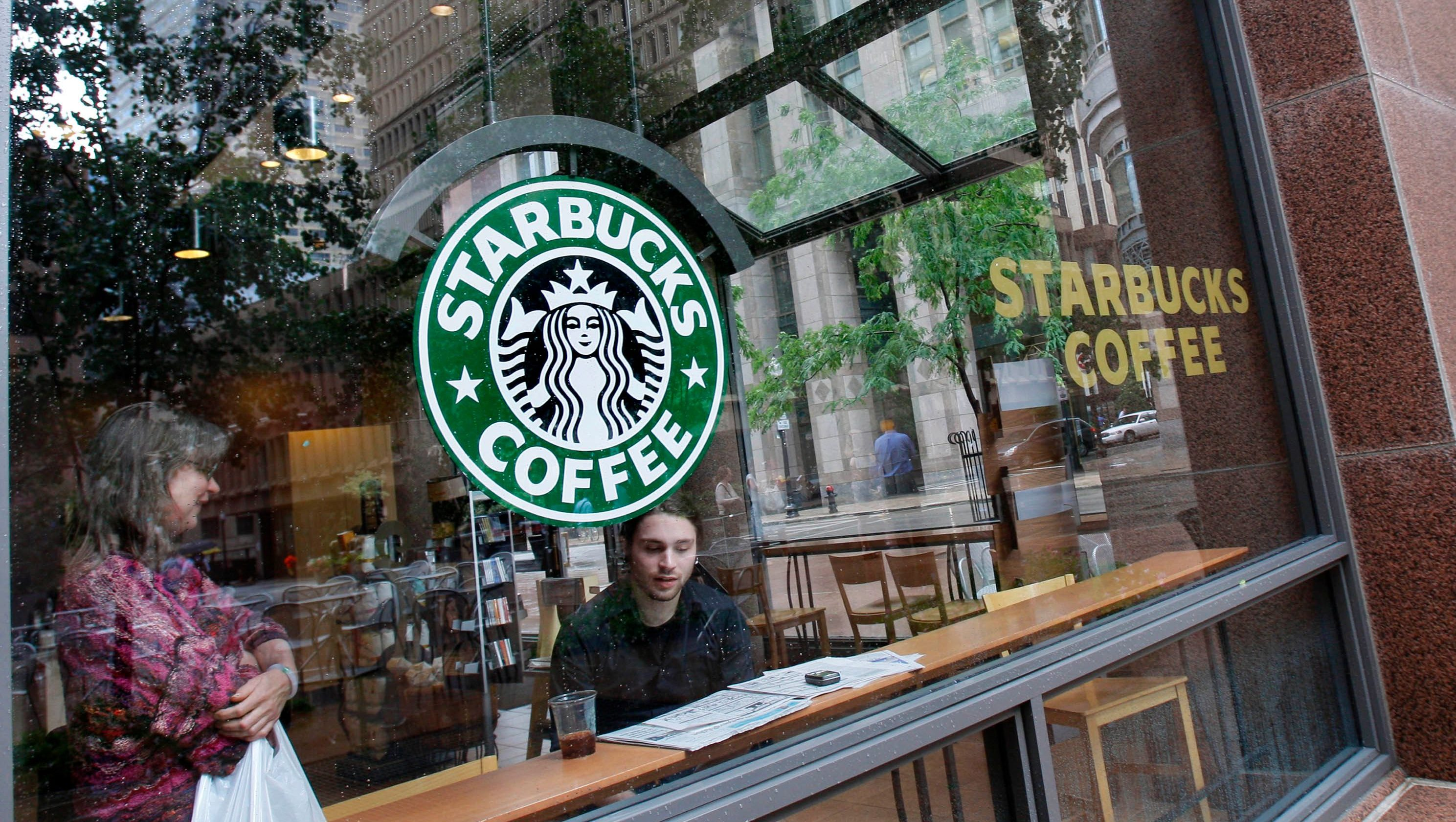 Patrons sit inside a Starbucks store in downtown Boston Tuesday, July 1, 2008. Starbucks Corp. said Tuesday it will close 600 stores in the United States in the next year and cut back the number of new stores it had planned to open. (AP Photo/Elise Amendola)