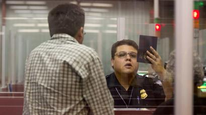 A Customs and Border Protection officer checks the passport of a non-resident visitor to the United States inside immigration control at McCarran International Airport