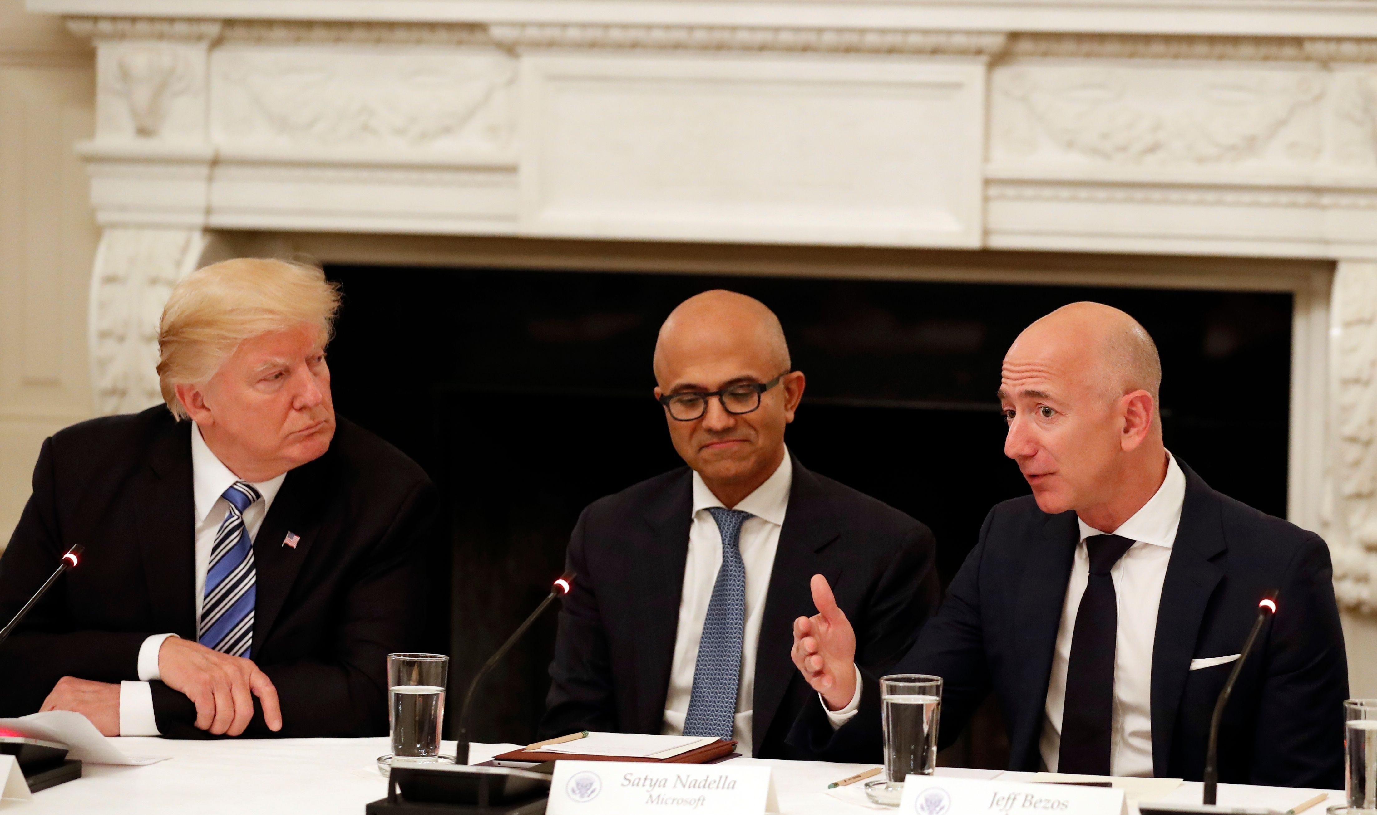 President Donald Trump, left, and Satya Nadella, Chief Executive Officer of Microsoft, center, listen as Jeff Bezos, Chief Executive Officer of Amazon, speaks during an American Technology Council roundtable in the State Dinning Room of the White House, Monday, June 19, 2017, in Washington. (AP Photo/Alex Brandon)