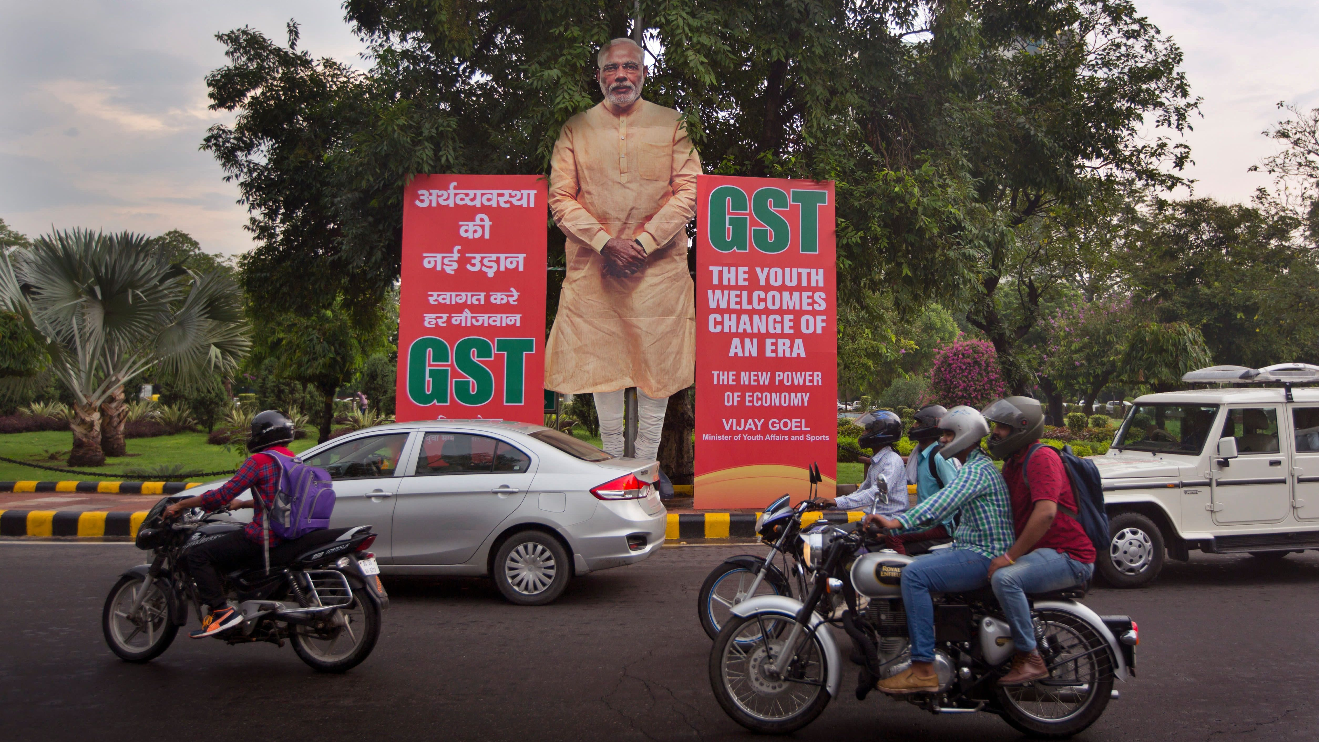 Indian commuters drive past a huge cutout of Indian Prime Minister Narendra Modi next to Goods and Services Tax (GST) banners in New Delhi, India, Friday, June 30, 2017. From July 1 Indian government is introducing a new tax regime called GST, a single, nationwide tax replacing a complicated mix of state and federal taxes and will change the cost of nearly everything people buy. (AP Photo/Manish Swarup)