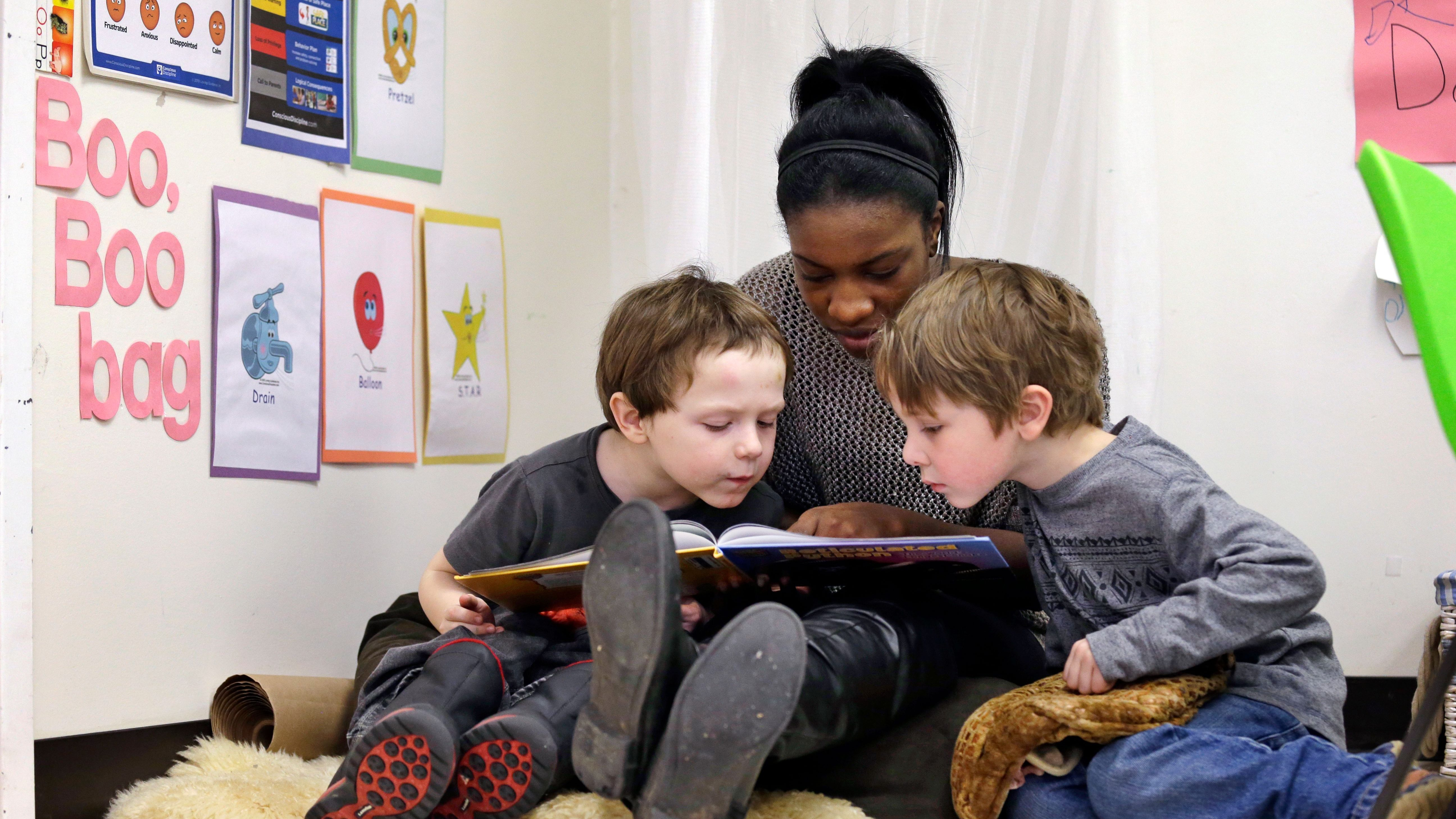 In this photo taken Feb. 12, 2016, assistant teacher D'onna Hartman, reads to Frederick Frenious, left, and Gus Saunders at the Creative Kids Learning Center, a school that focuses on pre-kindergarten for 4- and 5-year-olds, in Seattle.
