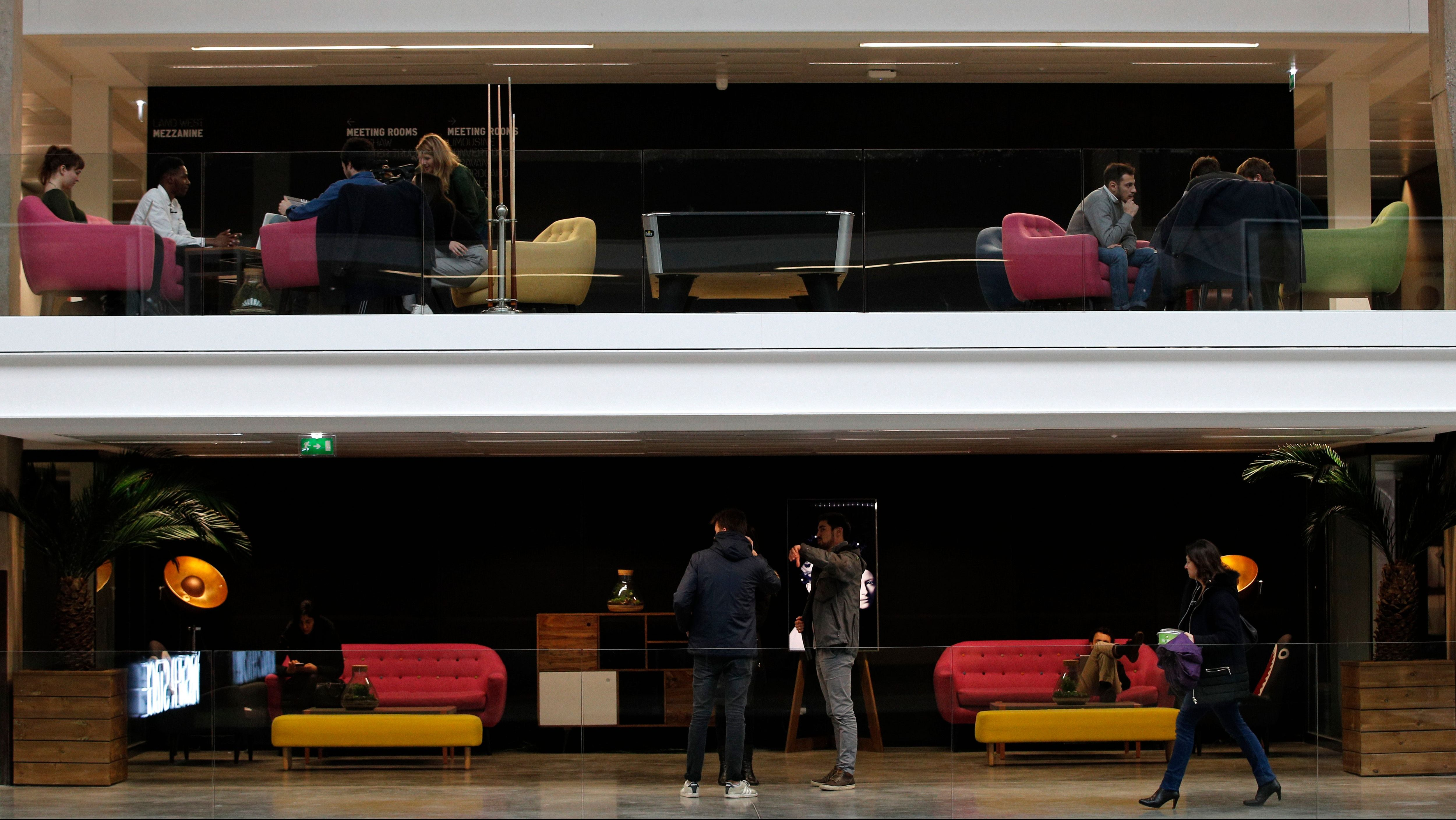 People attend meetings at the world's biggest start-up incubator Station F, in Paris, Wednesday, Jan. 31, 2018. For a glimpse at President Emmanuel Macron's vision for the new French economy, look no farther than Station F. Entrepreneurs don virtual reality goggles and share ideas with business angels in this old Paris train station-turned-startup incubator. (AP Photo/Christophe Ena)