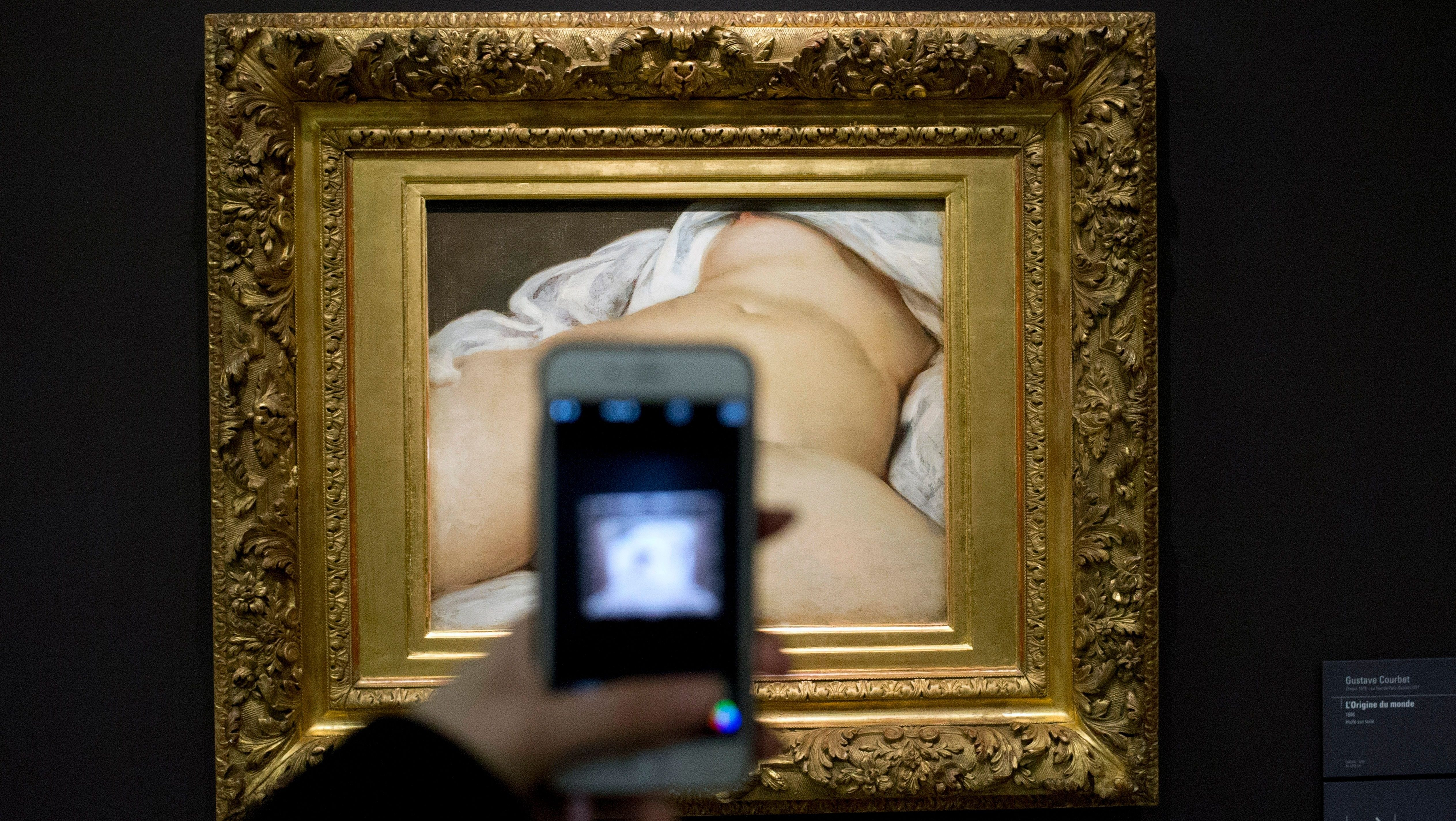 """FILE - In this Feb.12 2016 file photo, a visitor takes a picture of Gustave Courbet's 1866 """"The Origin of the World,"""" at Musee d'Orsay museum, in Paris. A French teacher, whose Facebook account was suspended in 2011 after he posted a photo of a famous 19th-century nude painting, is suing Thursday Feb. 1, 2018 the California-based social network Facebook for alleged """"censorship"""". Frederic Durand-Baissas, a 59-year-old Parisian teacher and art lover, posted a photo of """"The Origin of the World,"""" which depicts female genitalia. (AP Photo/Francois Mori, File)"""