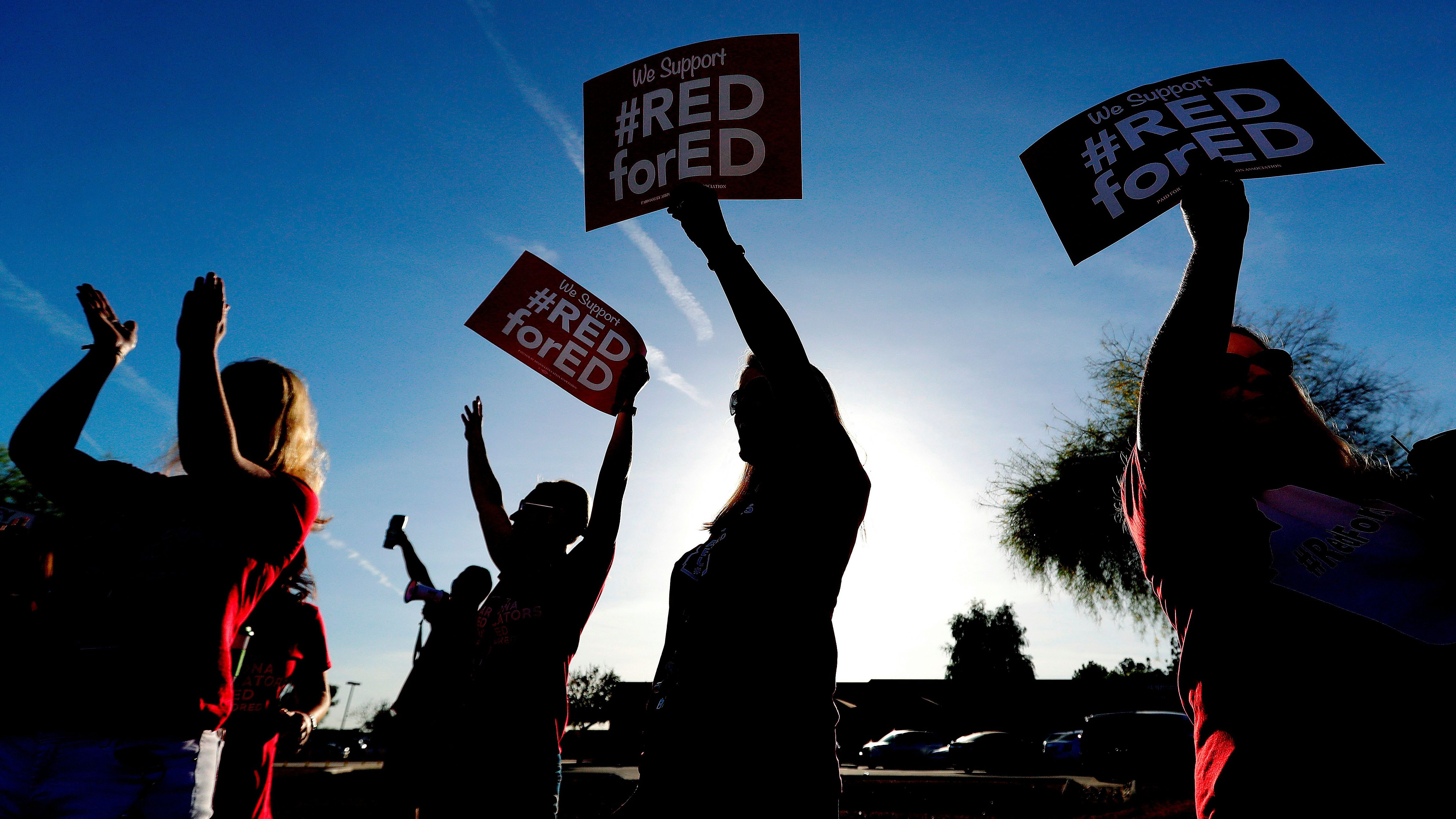 ILE - In this April 11, 2018, file photo, teachers at Humphrey Elementary school participate in a state-wide walk-in prior to classes in Chandler, Ariz. Arizona teachers began to vote Tuesday, April 17  on whether to walk off the job in their push for more funding for education. (AP Photo/Matt York, File)