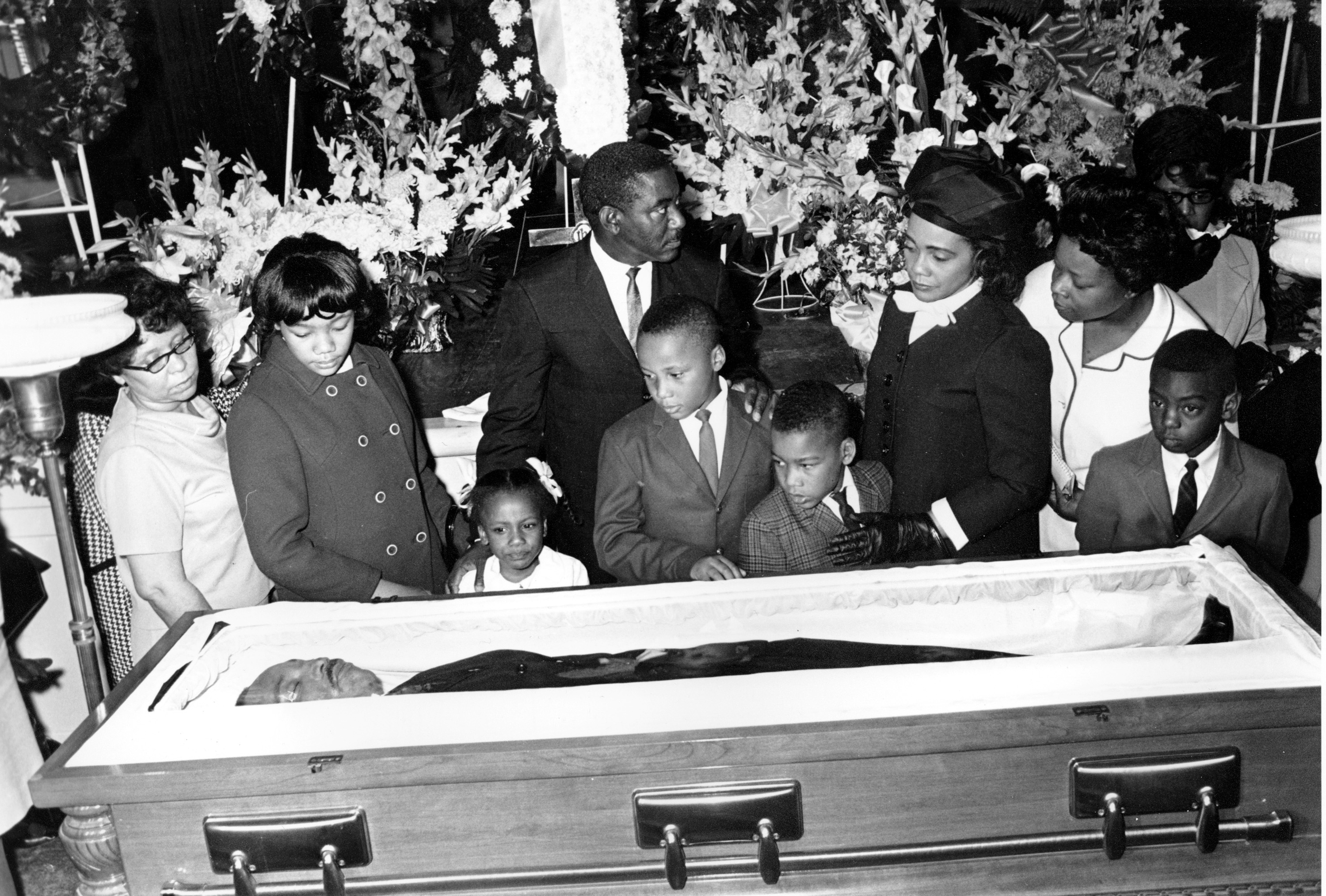 Coretta Scott King, wearing hat and gloves, and her four children view the body of her husband, slain civil rights activist leader Dr. Martin Luther King Jr., in Atlanta, Ga., on April 7, 1968. The children are, from left, Yolanda, 12, Bernice, 5, Martin III, 11, and Dexter 7. Dr. King was assassinated in Memphis, Tenn. on April 4. Other members in the photograph are not identified. (AP Photo)
