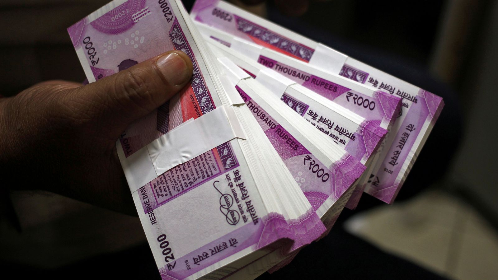 A cashier displays the new 2000 Indian rupee banknotes inside a bank in Jammu, November 15, 2016.