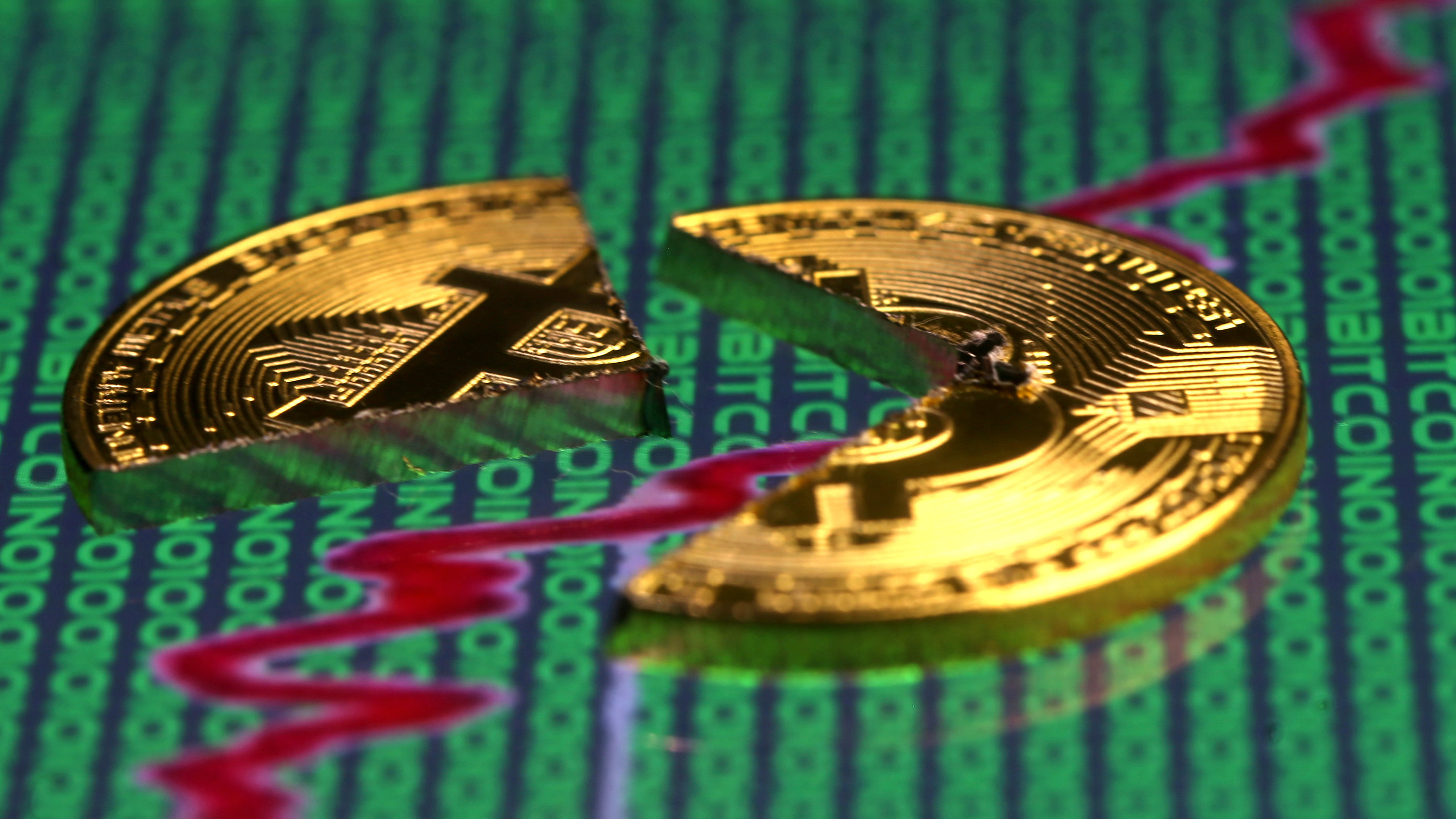 Broken representation of the Bitcoin virtual currency, placed on a monitor that displays stock graph and binary codes, are seen in this illustration picture, December 21, 2017.