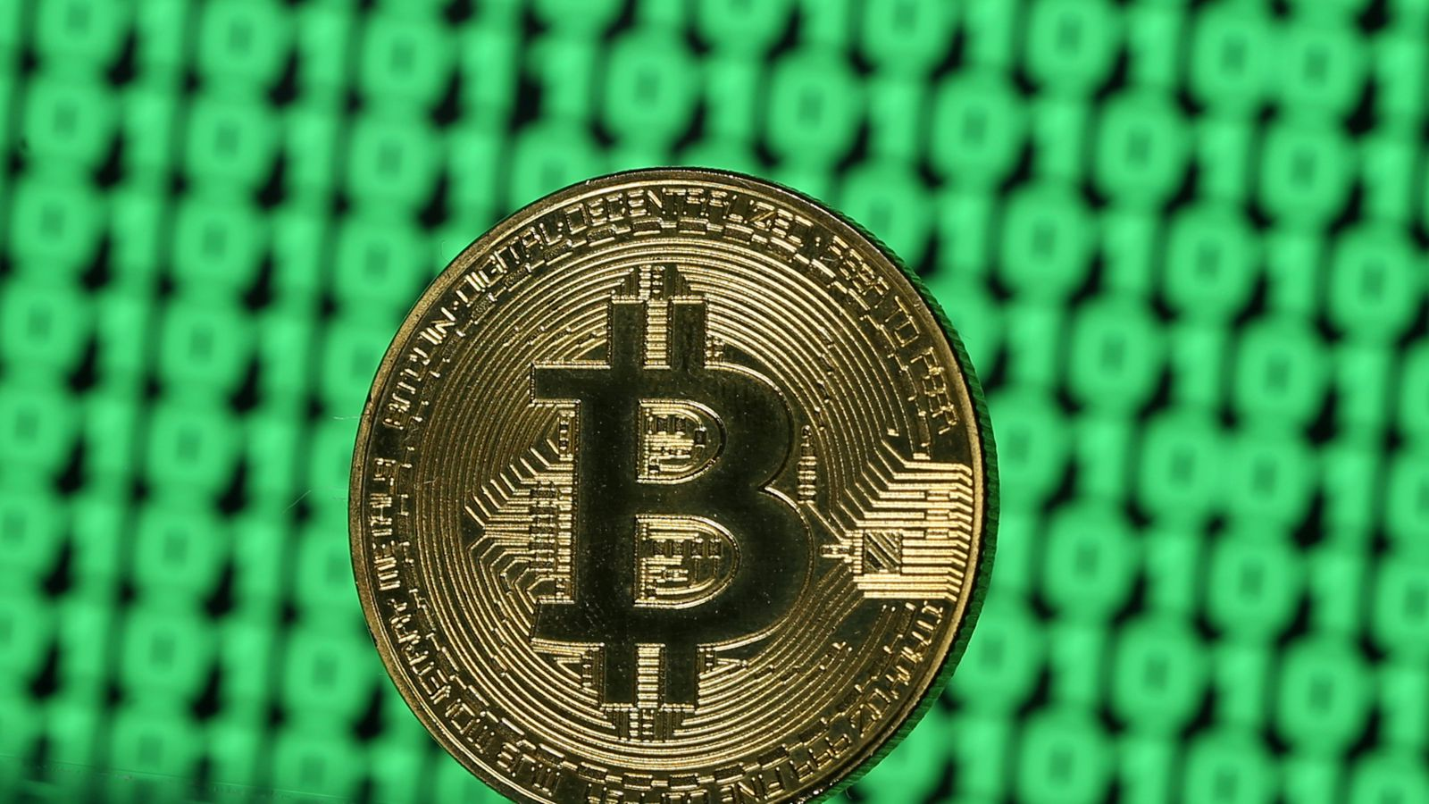 A token of the virtual currency Bitcoin is seen placed on a monitor that displays binary digits in this illustration picture, December 8, 2017