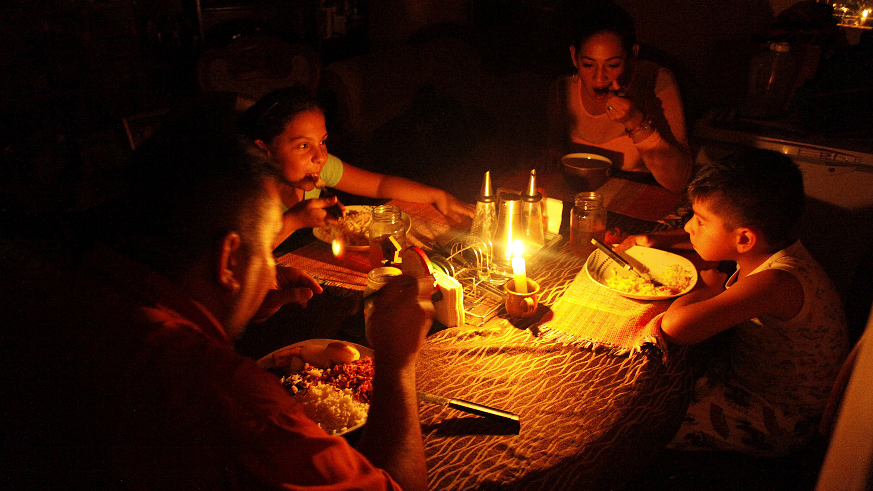 Lisney Albornoz (2nd R) and her family use a candle to illuminate the table while they dine, during a blackout in San Cristobal, Venezuela March 14, 2018. Picture taken March 14, 2018. REUTERS/Carlos Eduardo Ramirez - RC150CC4ECC0