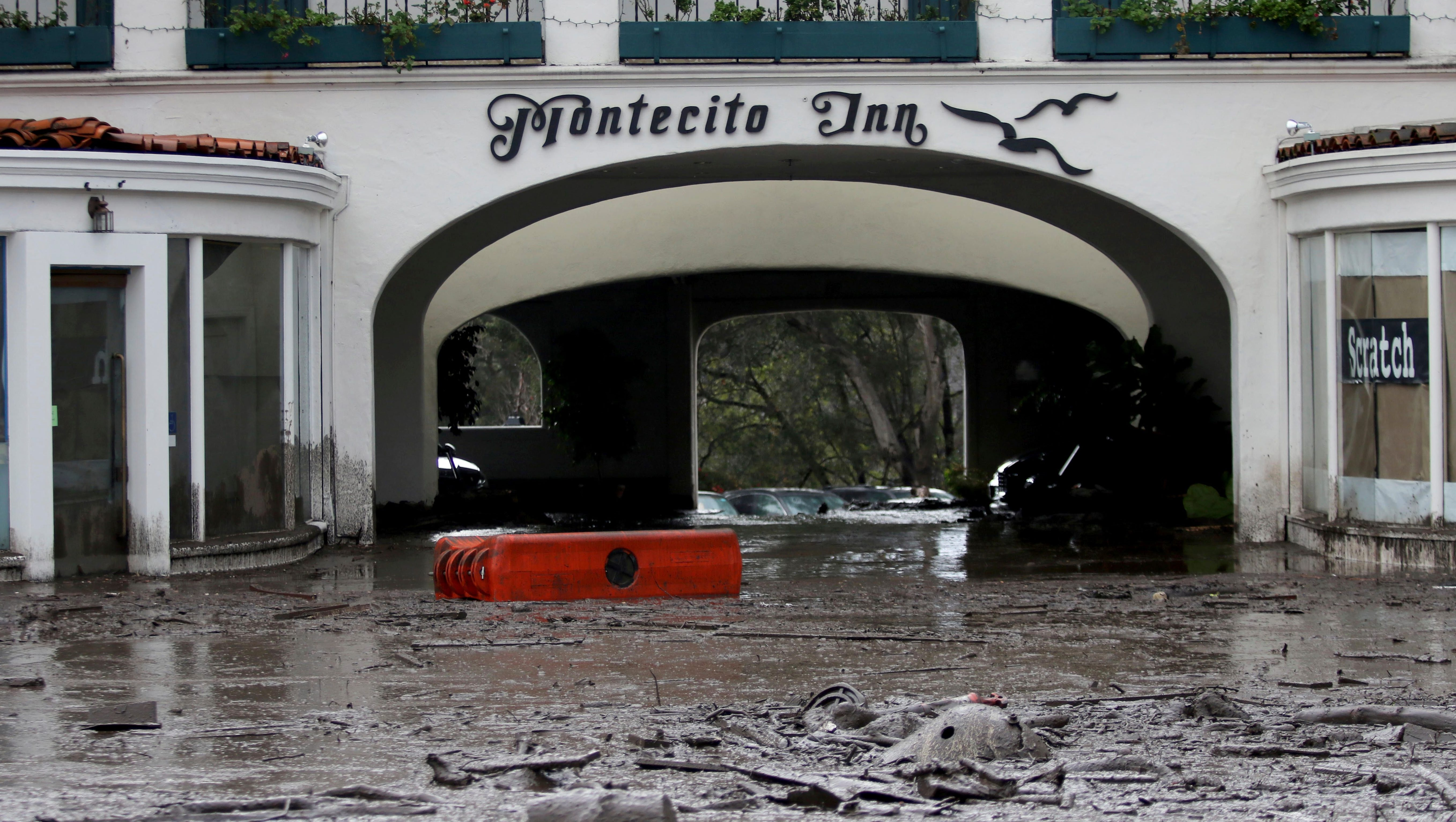 A flooded inn in Montecito, viewed from the outside with water flowing beneath its portico.