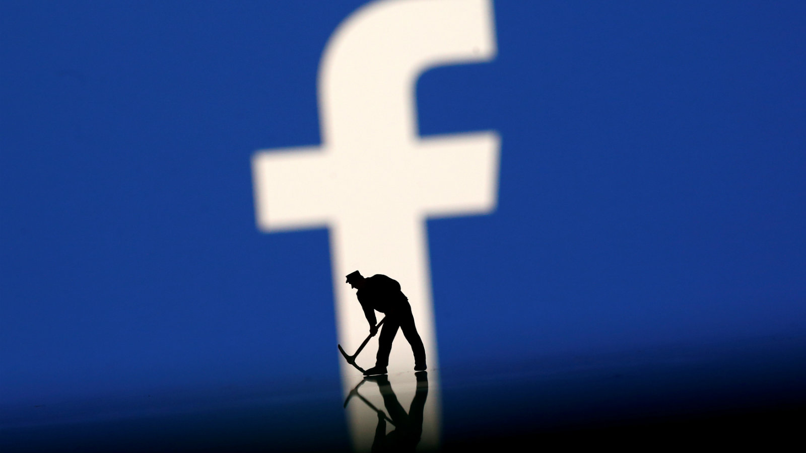 A figurine is seen in front of the Facebook logo in this illustration taken, March 20, 2018. /File Photo