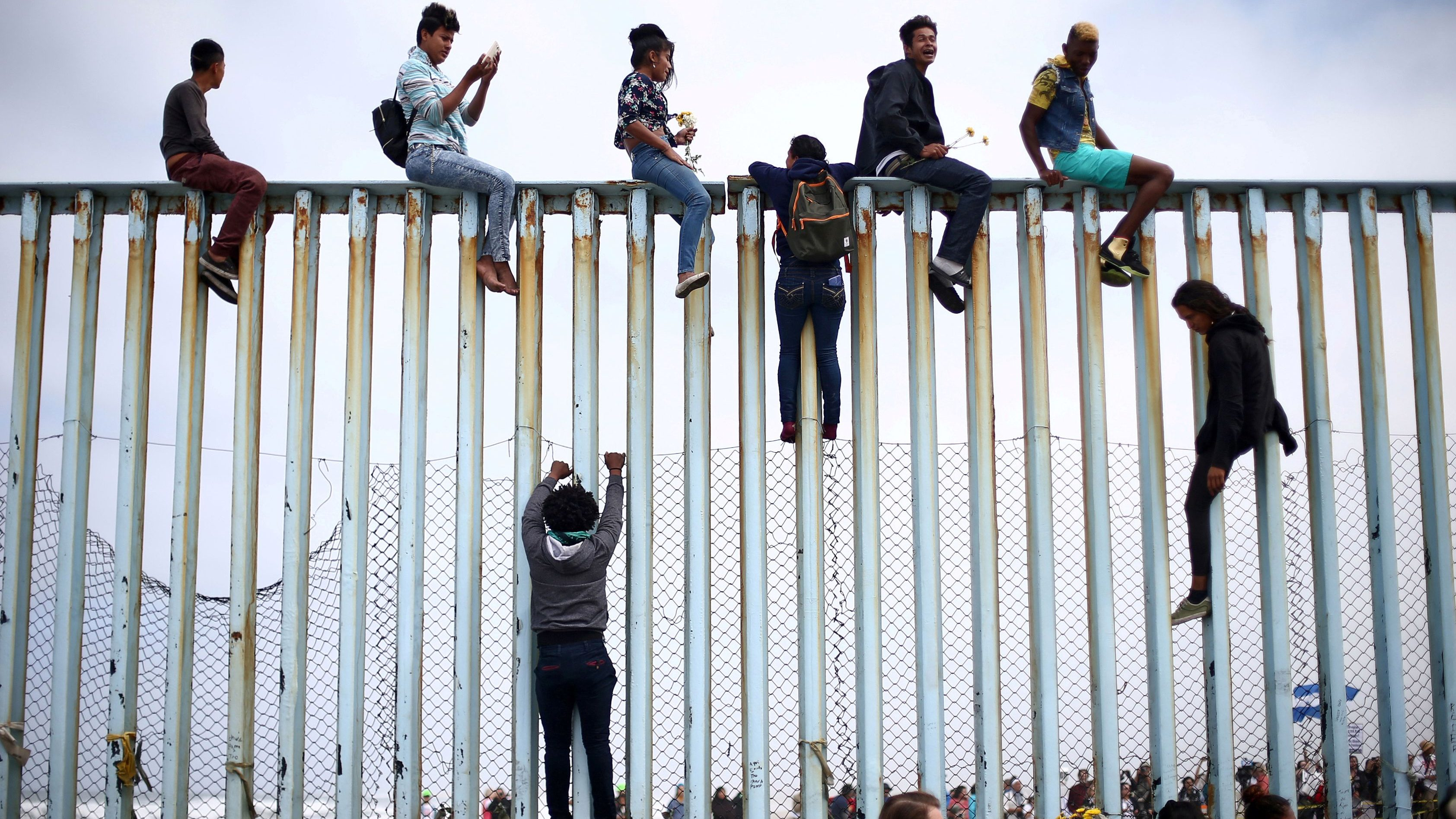 Members of a caravan of migrants from Central America climb up the border fence between Mexico and the U.S., as a part of a demonstration prior to preparations for an asylum request in the US
