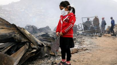 A child stands at the scene of a fire at 'Cantagallo' shanty town in Rimac district of Lima, Peru
