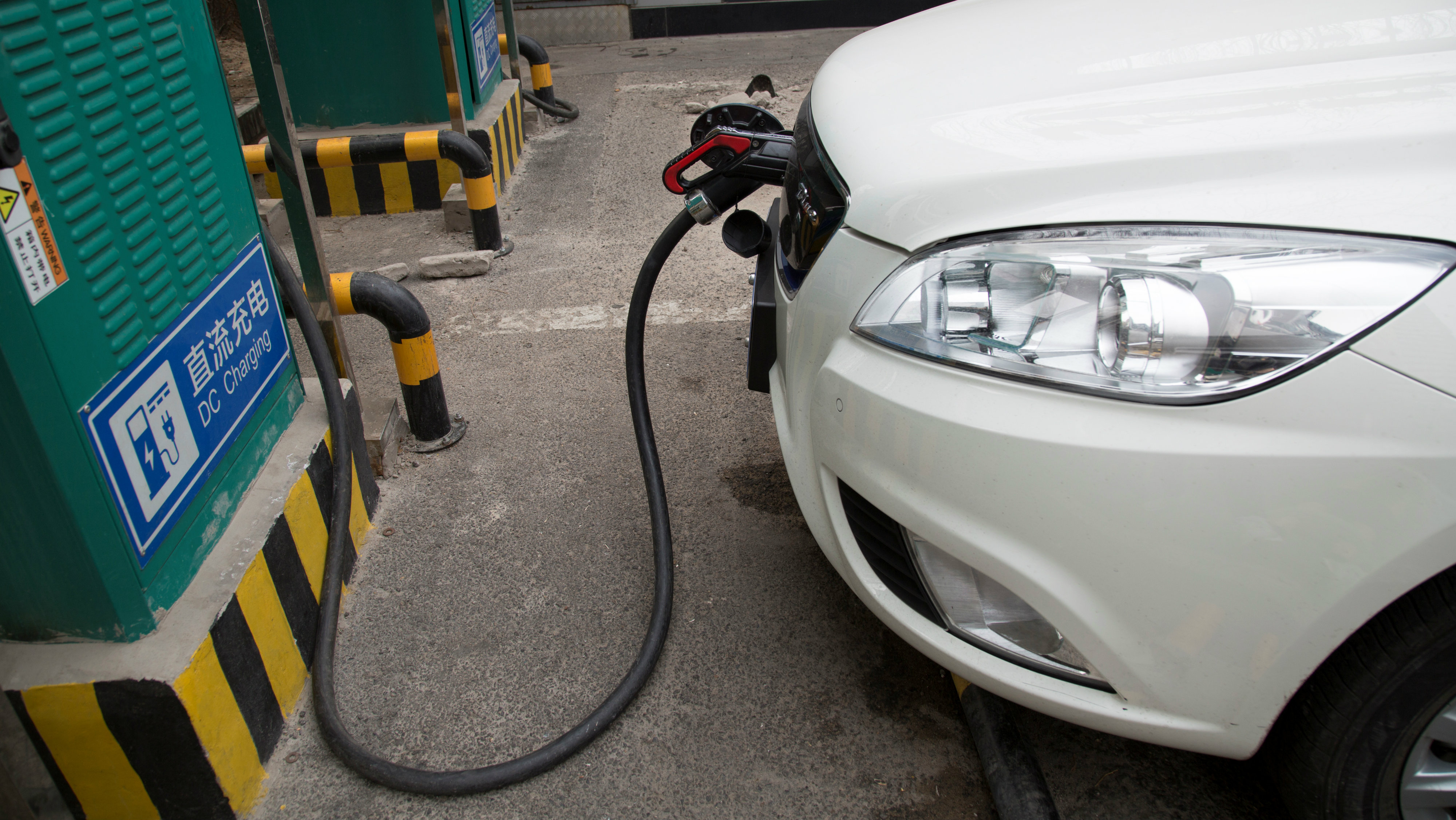 A charging cable is seen hooked to a car at a State Grid Corporation of China charging point for electric vehicles in Beijing, China March