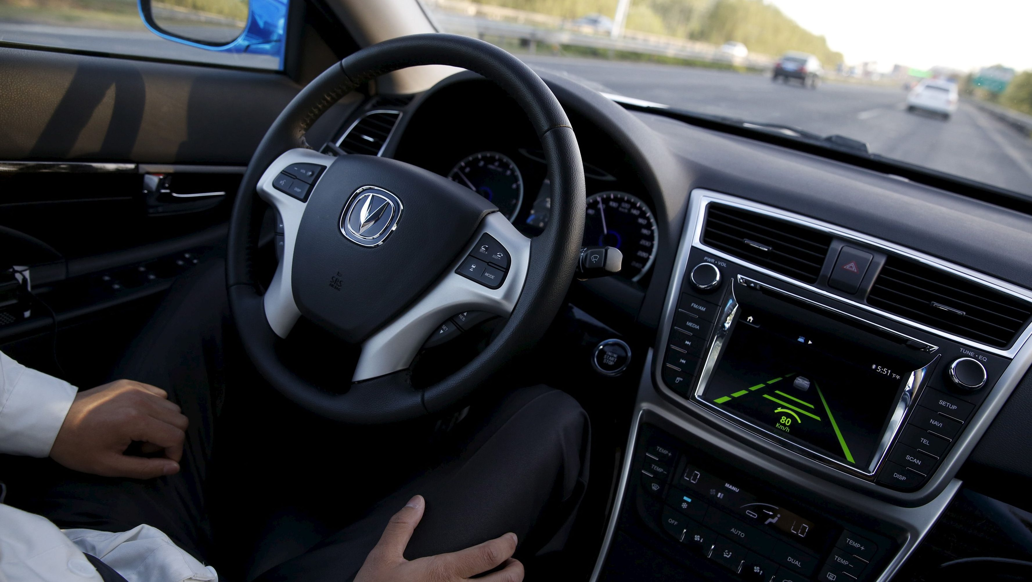 Li Zengwen, a development engineer at Changan Automobile, removes his hands from the steering wheel while the car is on self-driving mode during a test drive on a highway in Beijing, China, April 16, 2016.